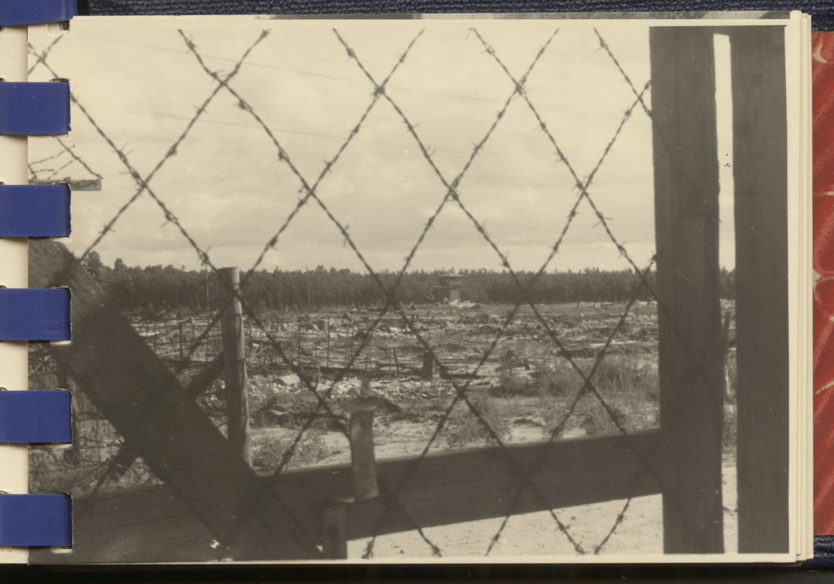 One page from a small photograph booklet containing images of Bergen-Belsen shortly after liberation.  View of Bergen-Belsen through barbed wire.