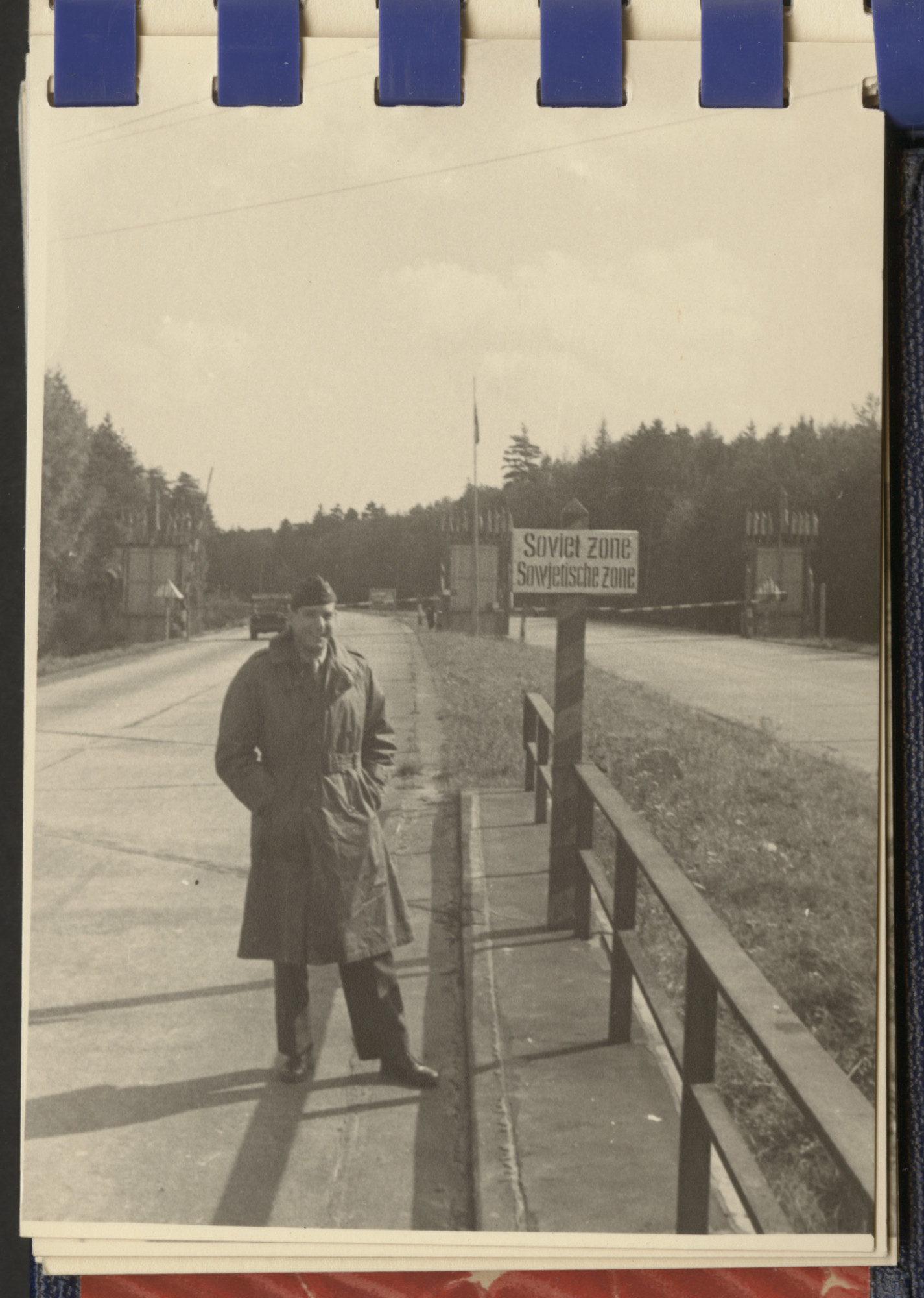 One page from a small photograph booklet containing images of Bergen-Belsen shortly after liberation.  A British [?] soldier poses by a sign indicating the Soviet zone.
