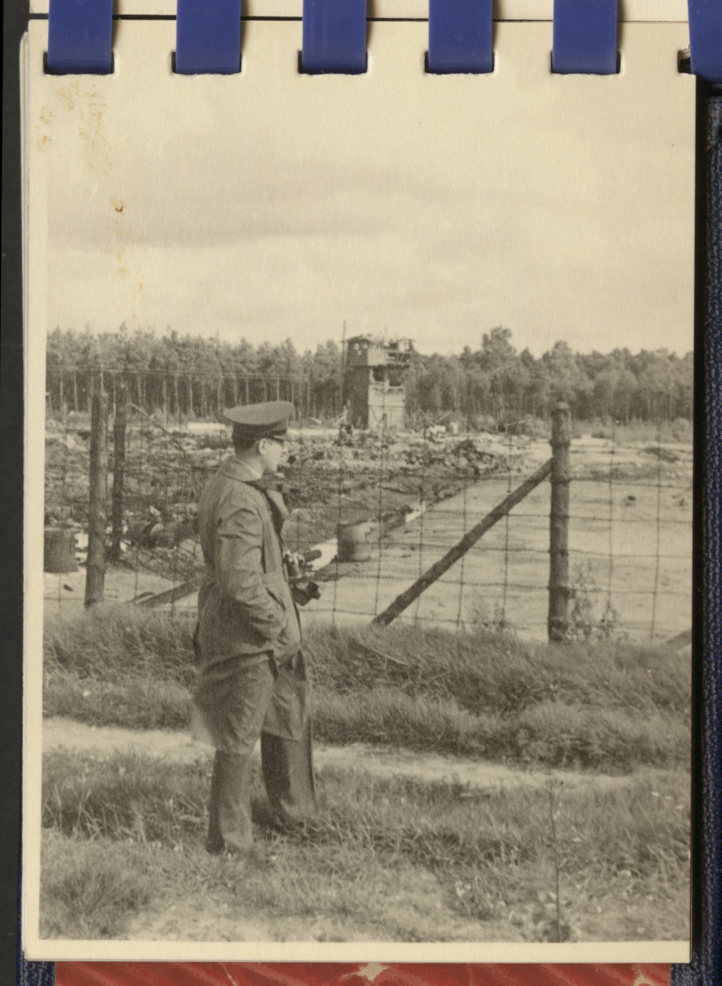 One page from a small photograph booklet containing images of Bergen-Belsen shortly after liberation.  A British [?] officer  looks out over the liberated camp.