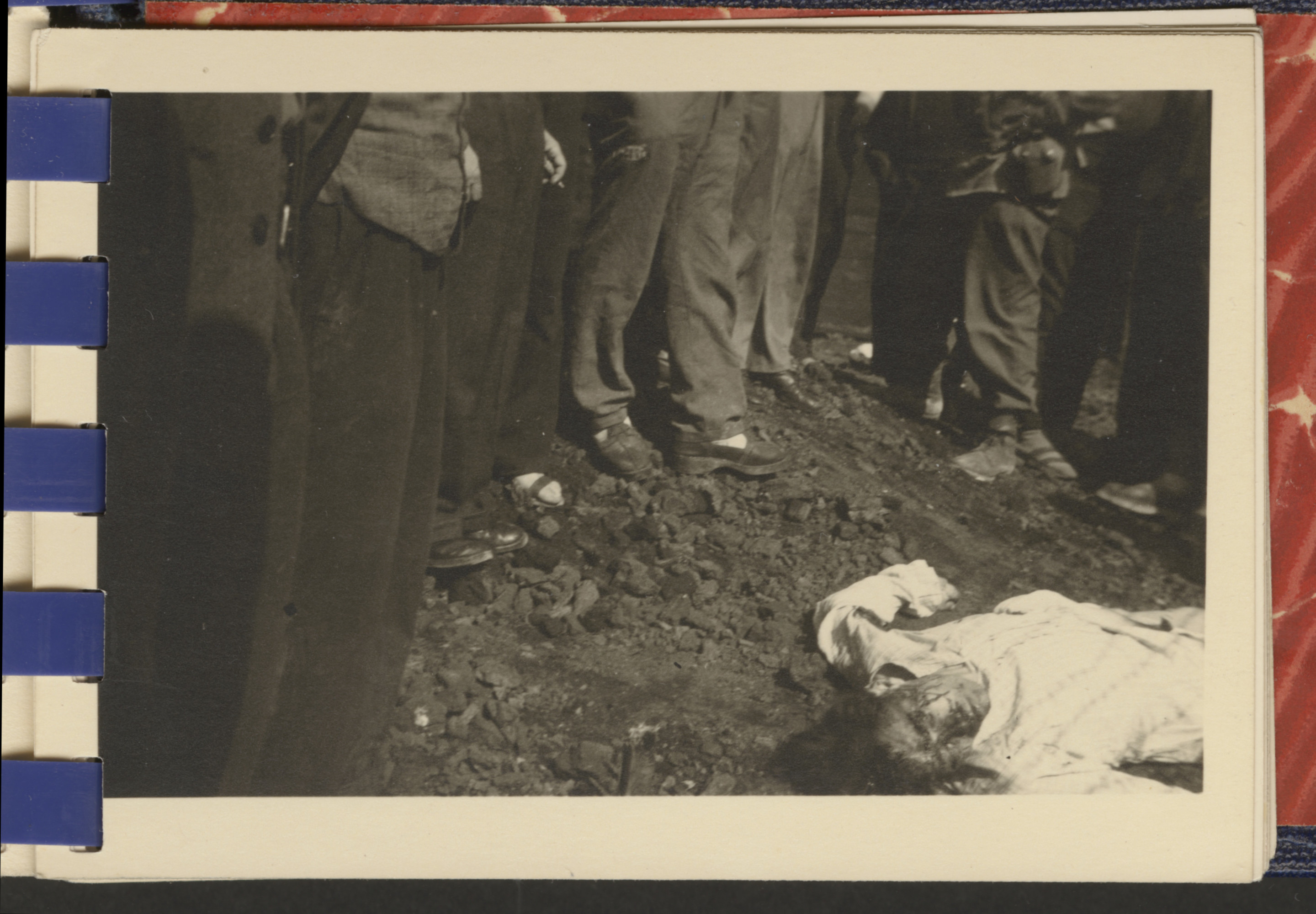One page from a small photograph booklet containing images of Bergen-Belsen shortly after liberation.  British soldiers view the corpse of an unknown individual.