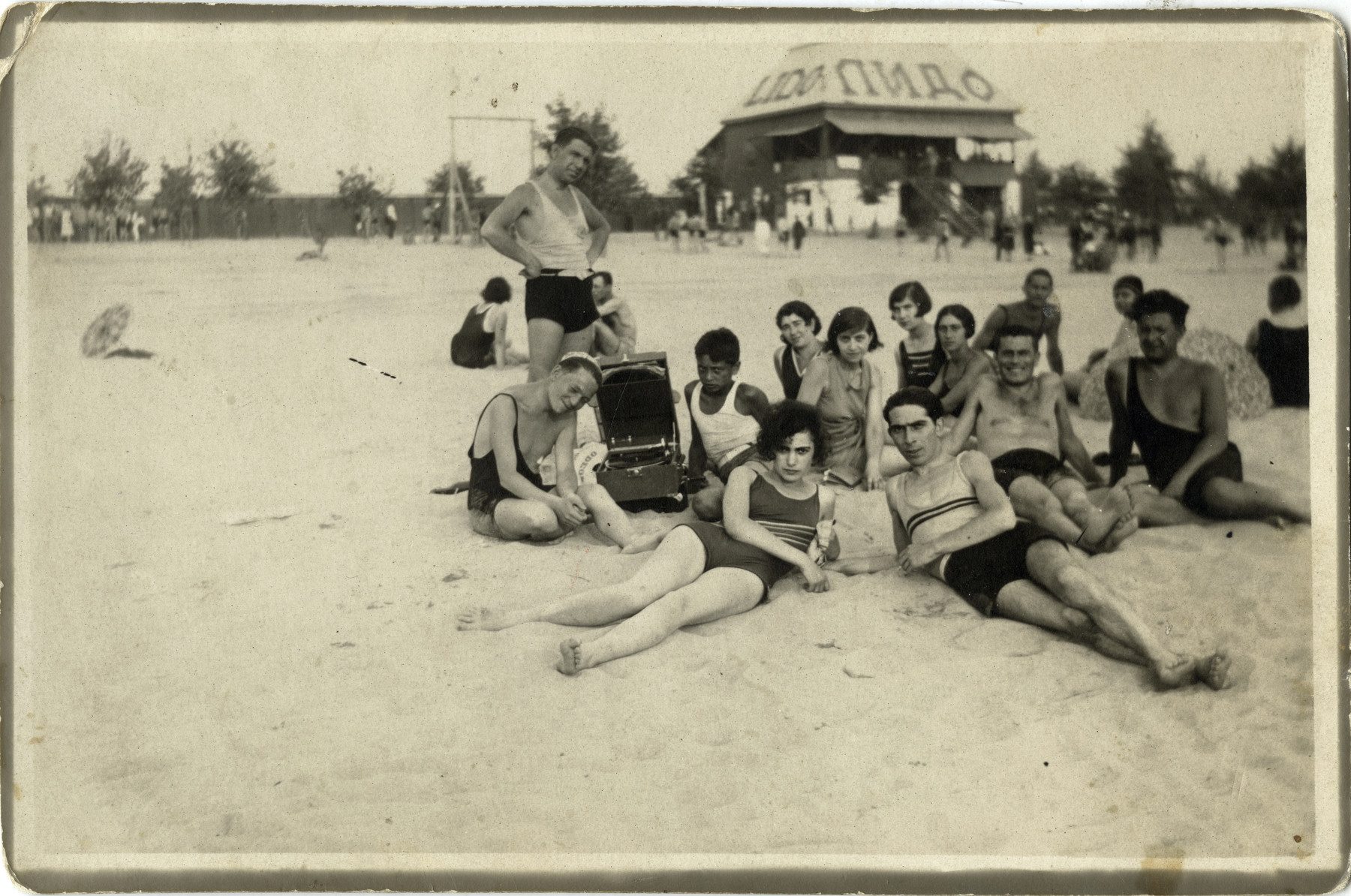 A group of Yugoslavs relax on a beach in Belgrade.  Yitzhak (Izak) Manojlvic (first row on the right) on the beach with future wife Hilda Gerstel (first row on the left) in front of Lido, Belgrade.