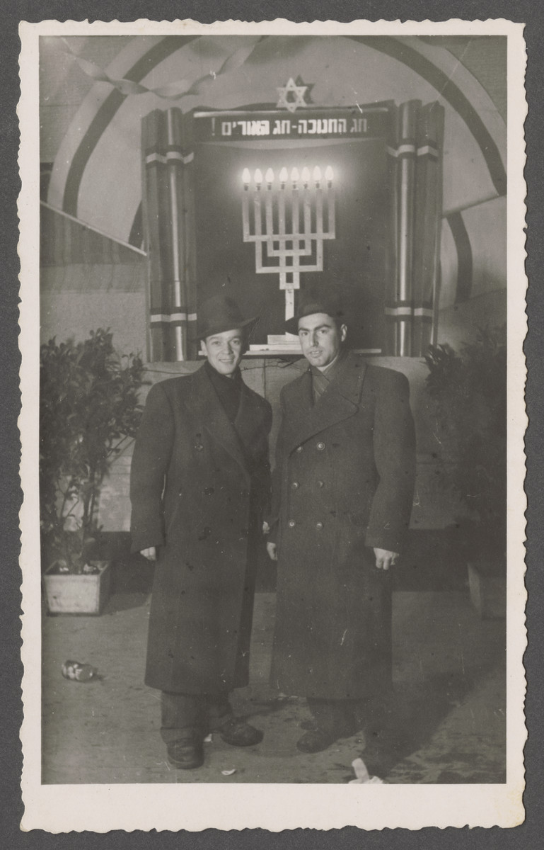 Joseph Pinczuk and a friend stand by a Hannukah display,
