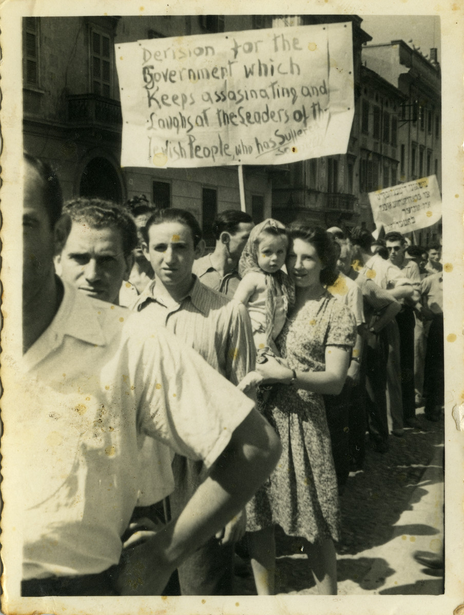 Jews from the Cremona displaced persons camp hold an anti-British demonstration.  Shulamit Kagan is pictured in the arms of her mother Lisa.
