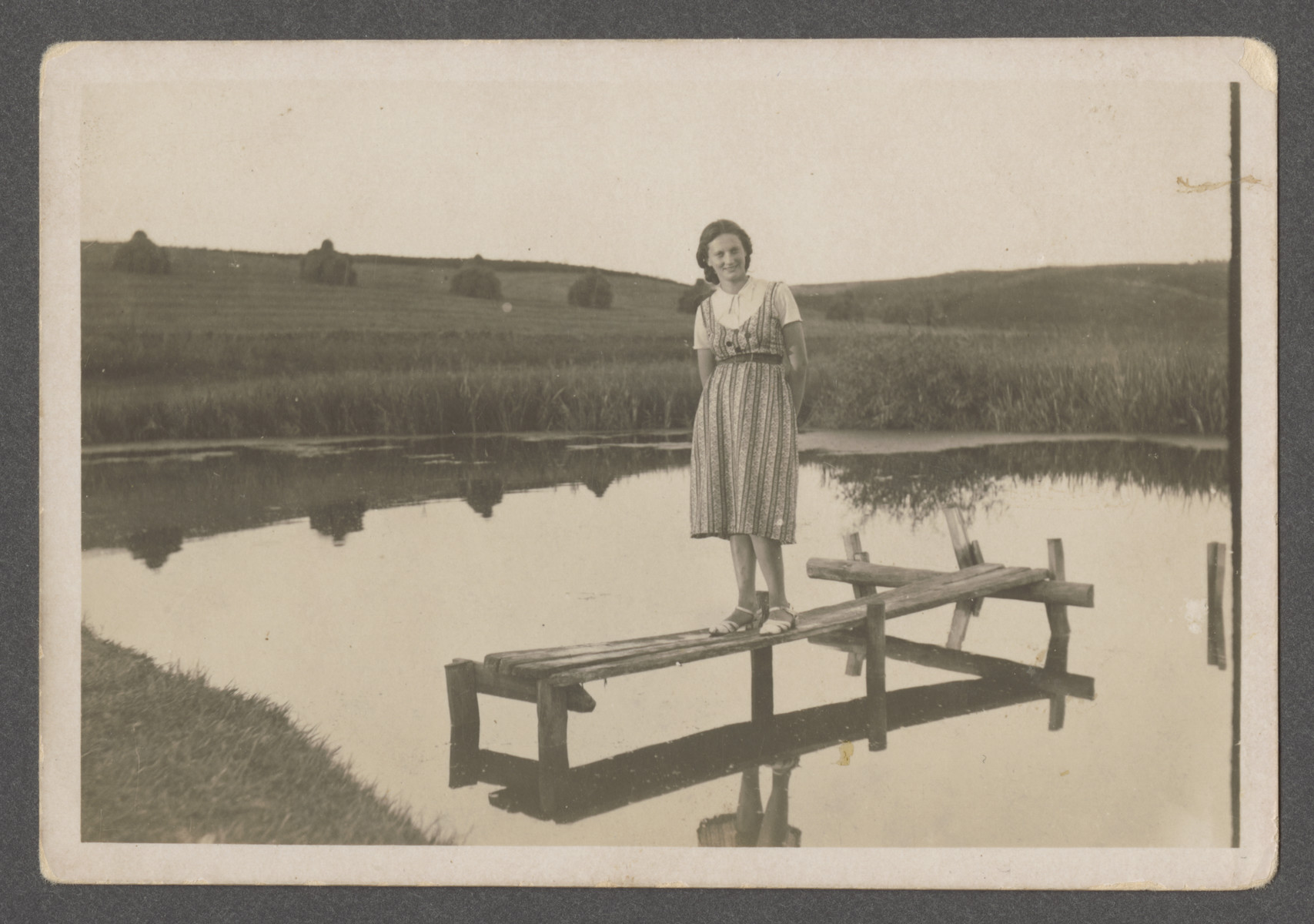Fania Scwarczman stands on a small wooden structure on a river in prewar Aleksandria