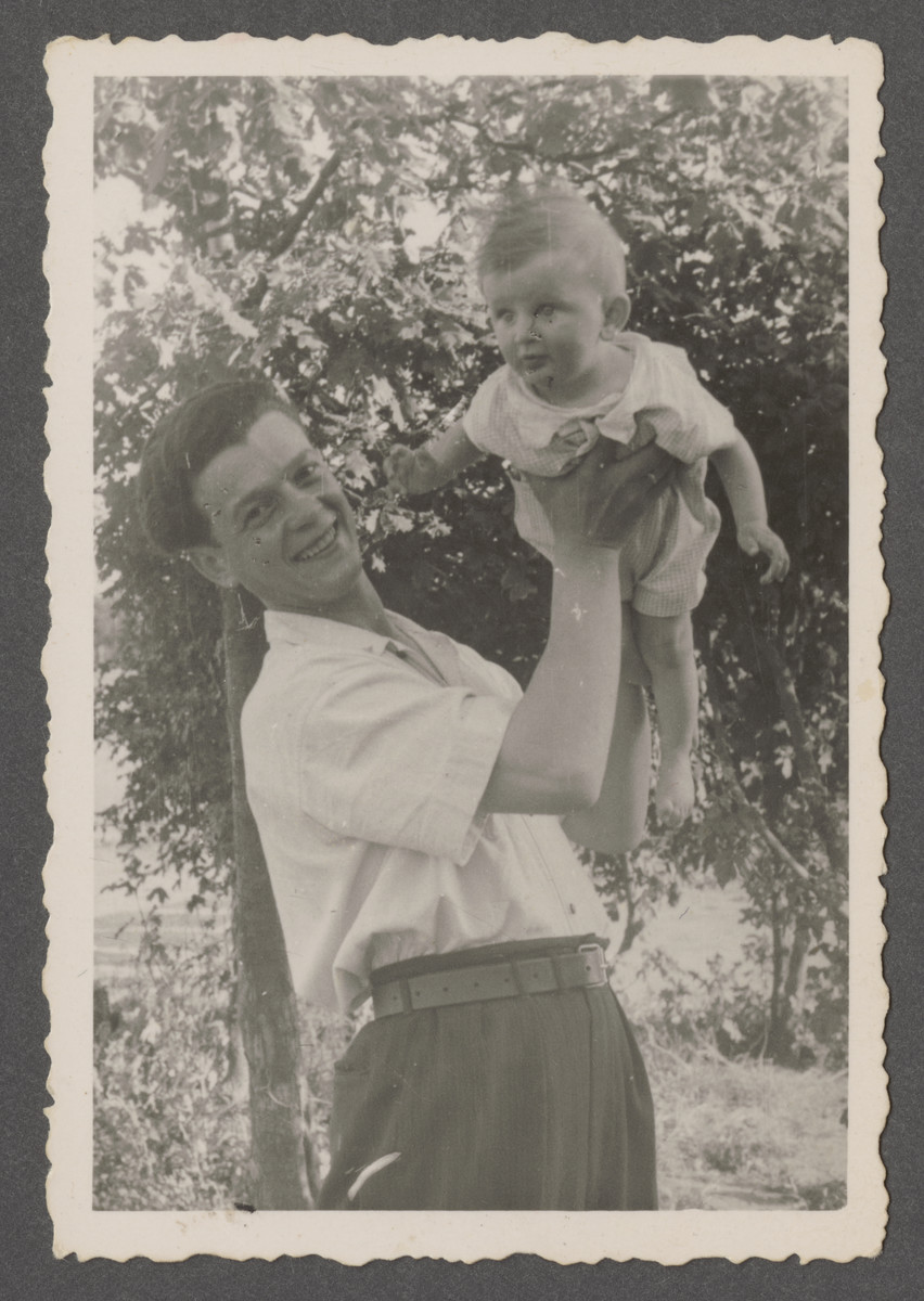Joseph Pinczuk pose holds his infant son Aaron Jonah high in the air in the Linz displaced persons camp.