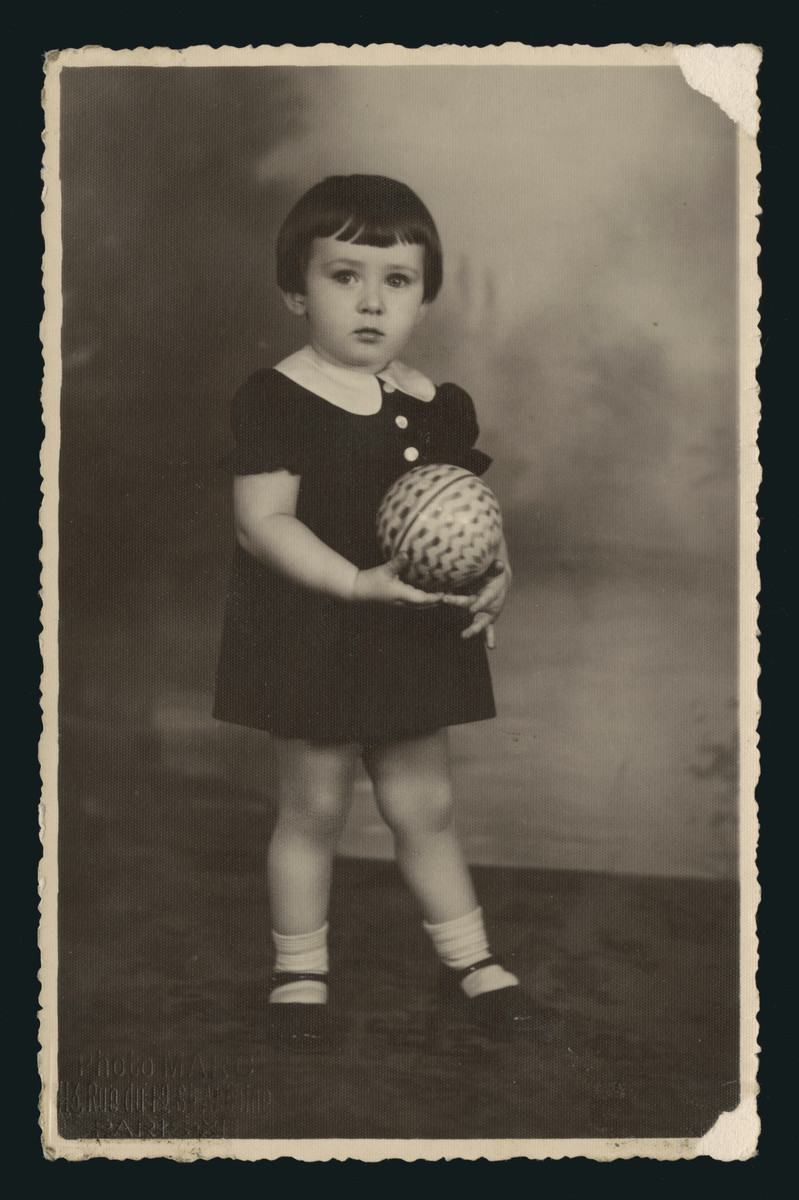Studio portrait of Denise Rewzin holding a ball.  She is the daughter of a family from Eisiskes.