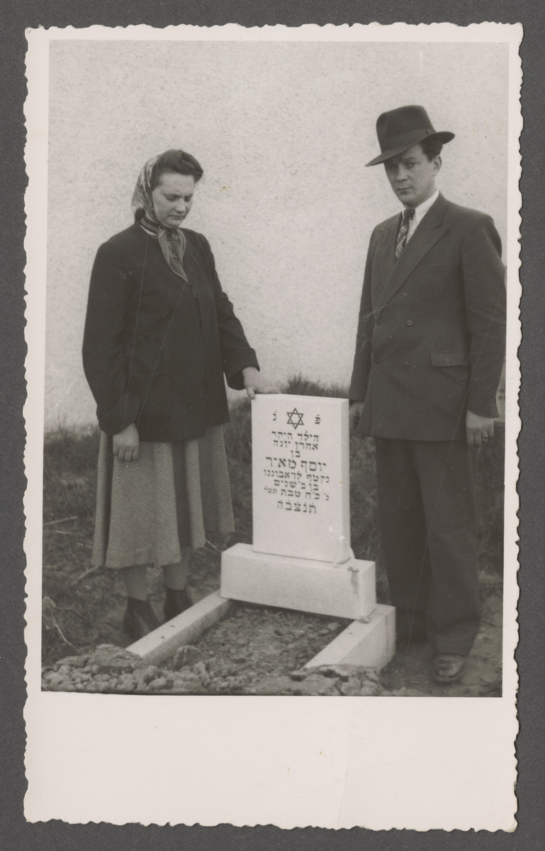 Joseph and Fania Pinczuk pose by the grave of their infant son Aaron Jonah in the Linz displaced persons camp.
