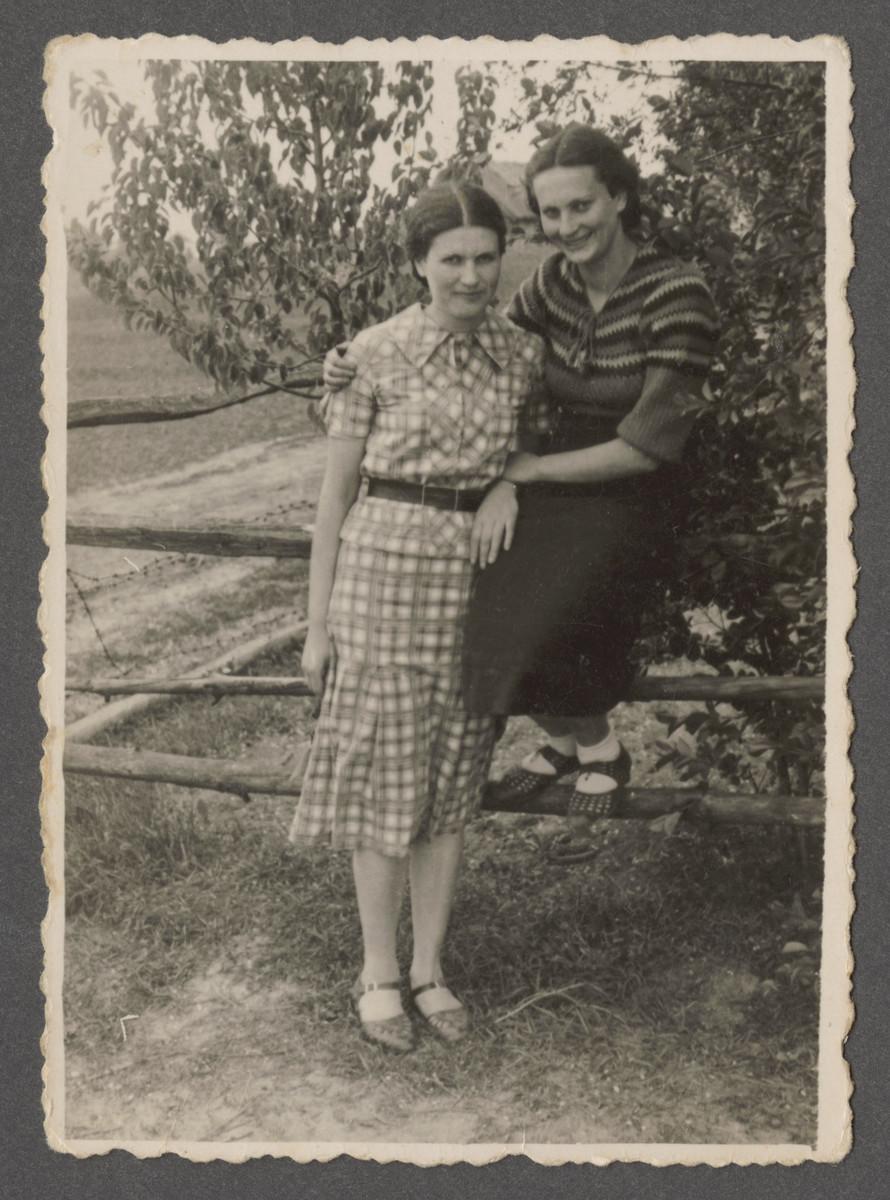 Fania and Sonia Szwarczman poses by a wooden fence in prewar Aleksandria.