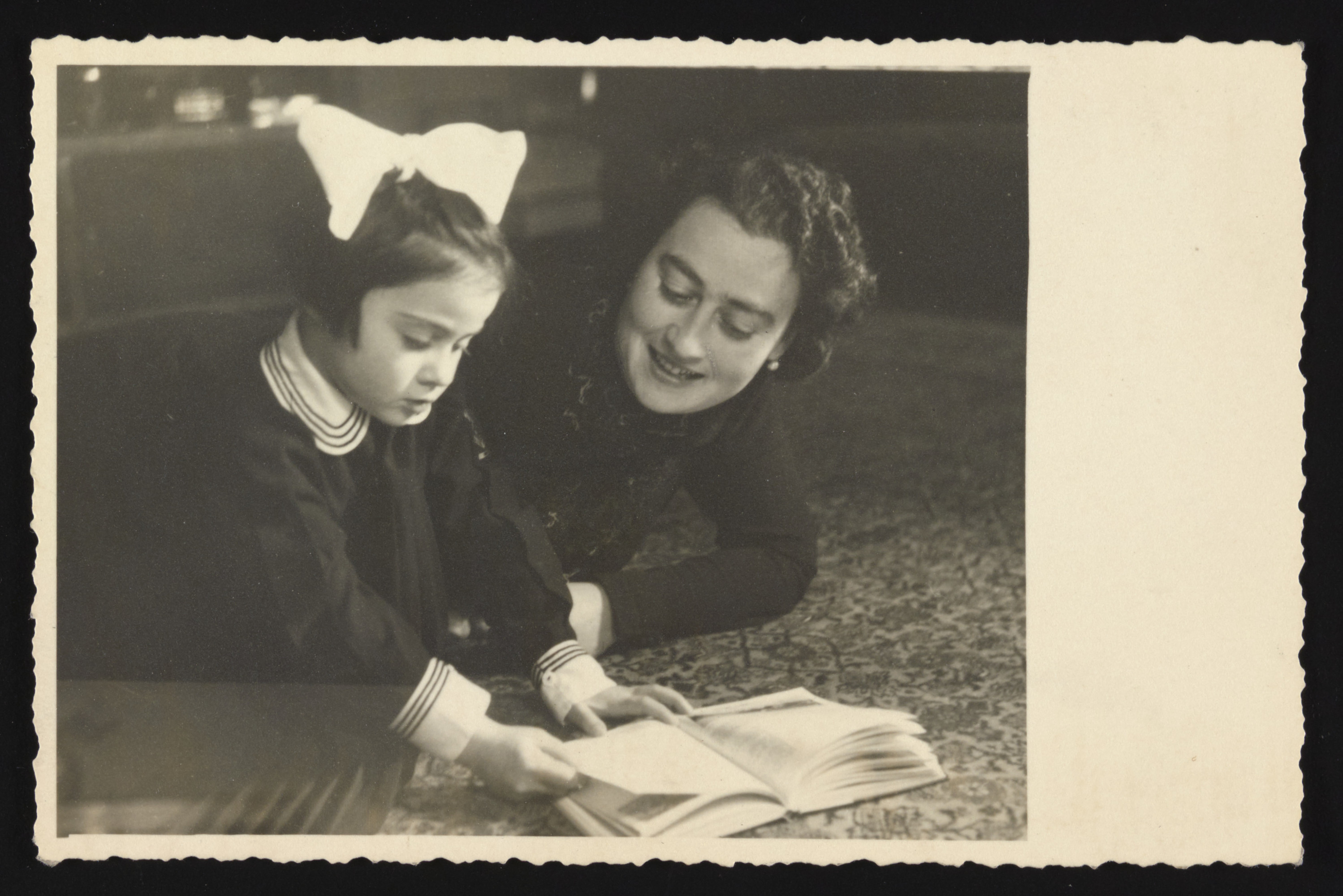 Tamar (Ruth) and her mother Hana read a book in their home in Zagreb, Yugoslavia shortly before they fled to the Italian zone.