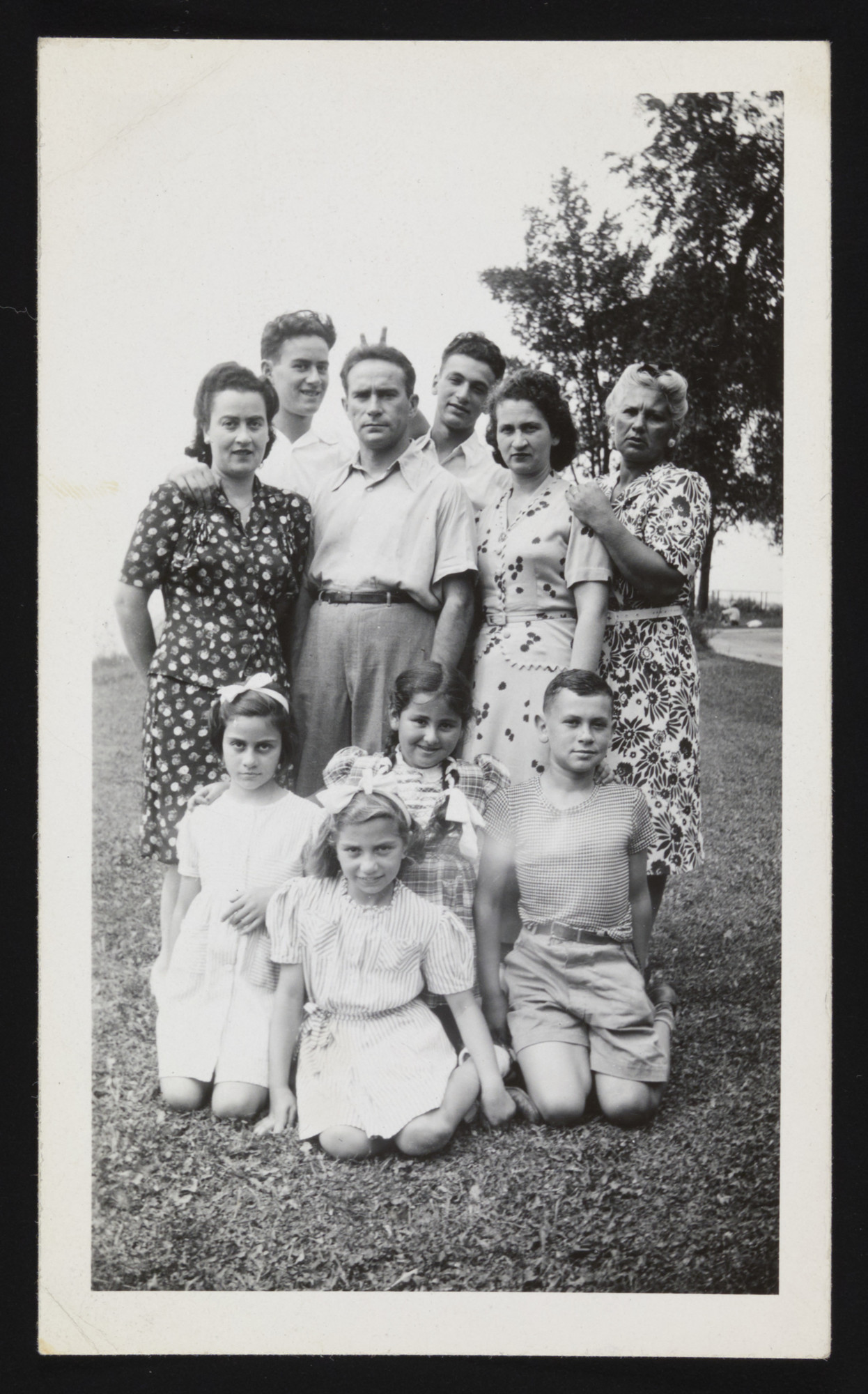 The Hendel family poses for a group portrait in Fort Ontario.   Pictured: First row--Ruth, Gisele Kremer, Mindy (an American relative) and Vilko.  Second Row: Hana, David, Eisik, Herman, and Berta