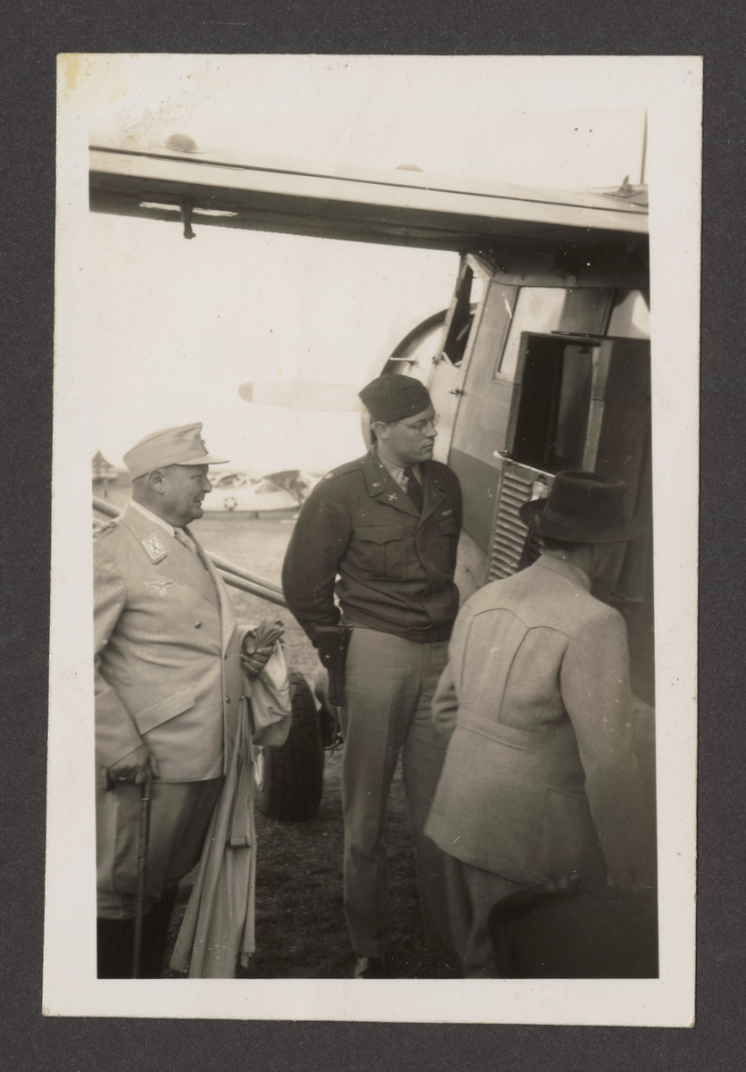 """Hermann Goering waits to board the plane to  Camp Ashcan, a temporary prisoner-of-war camp housed in the Palace Hotel at Mondorf-les-Bains, Luxembourg.  The inscription on the back reads,  """"What're you waiting for Herman--get in!!"""""""