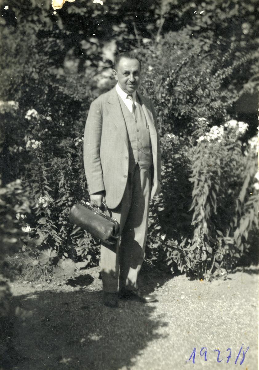 Dr. Josef Kohn stands outside holding his doctor's bag.