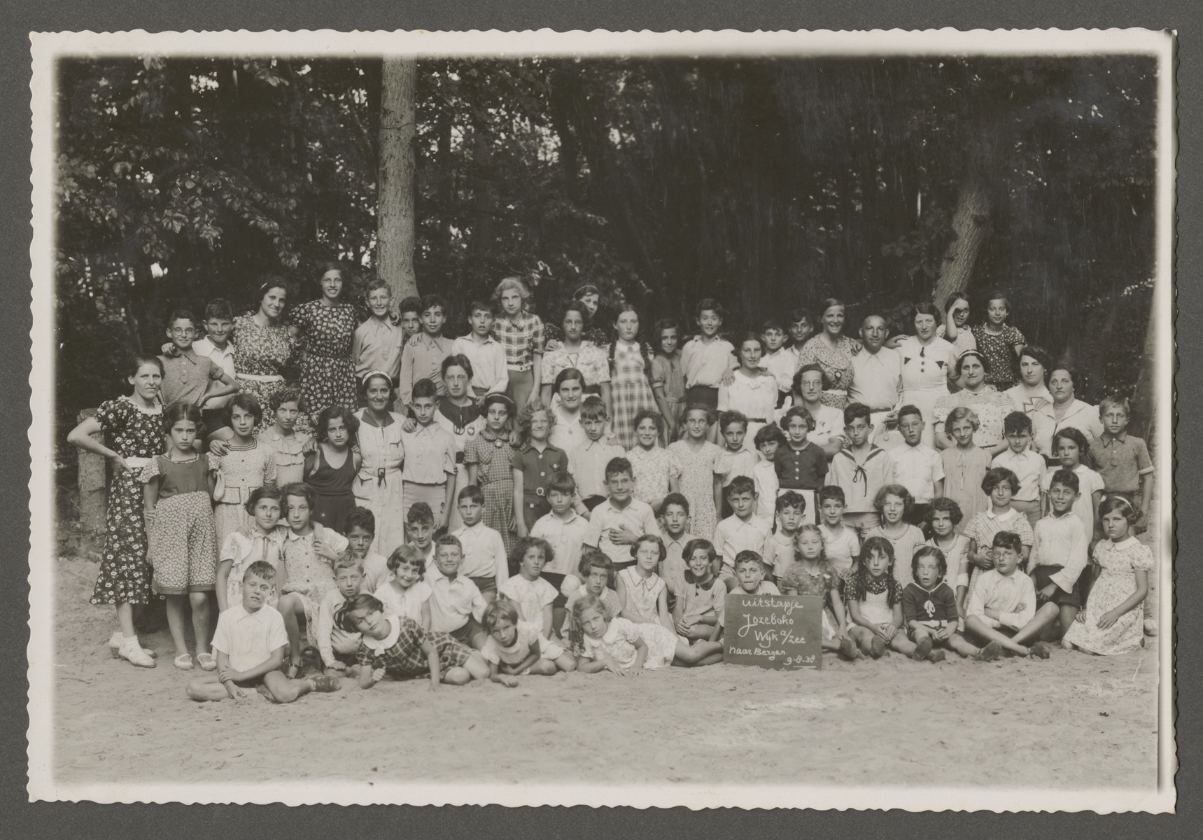 Group portrait of school children in a school in Amsterdam.  Among those pictured is Henri Rodrigues (front row, holding the sign).  The third girl to the right of Henri is his sister, Elizabeth Rodrigues (later Cassuto).