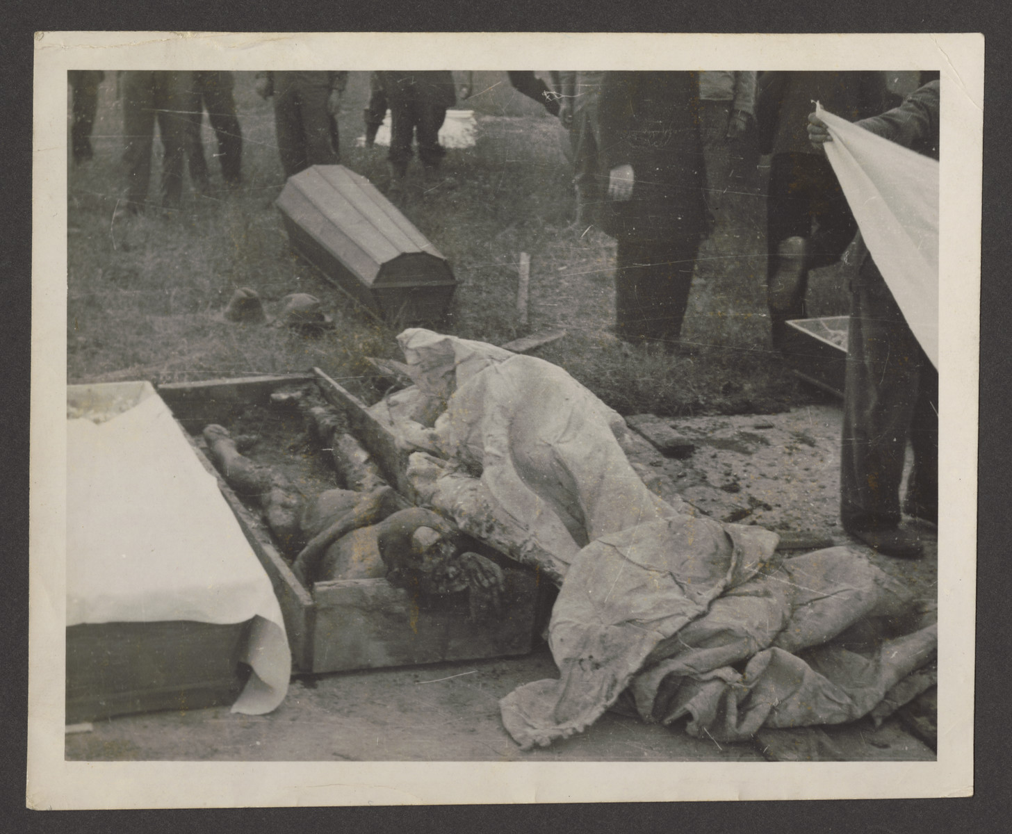 A corpse exhumed from a mass grave in Dachau lies in a rough coffin prior to reburial.