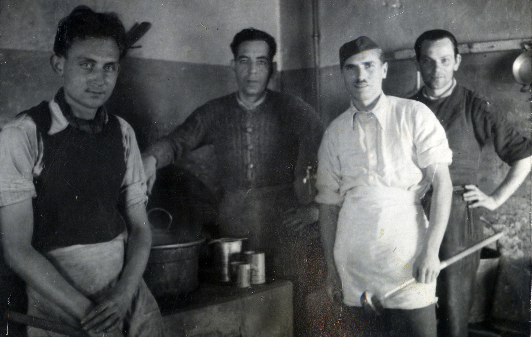 Four men pose in the kitchen at Ferramonti.  Ernest Hellinger is pictured second from the right.
