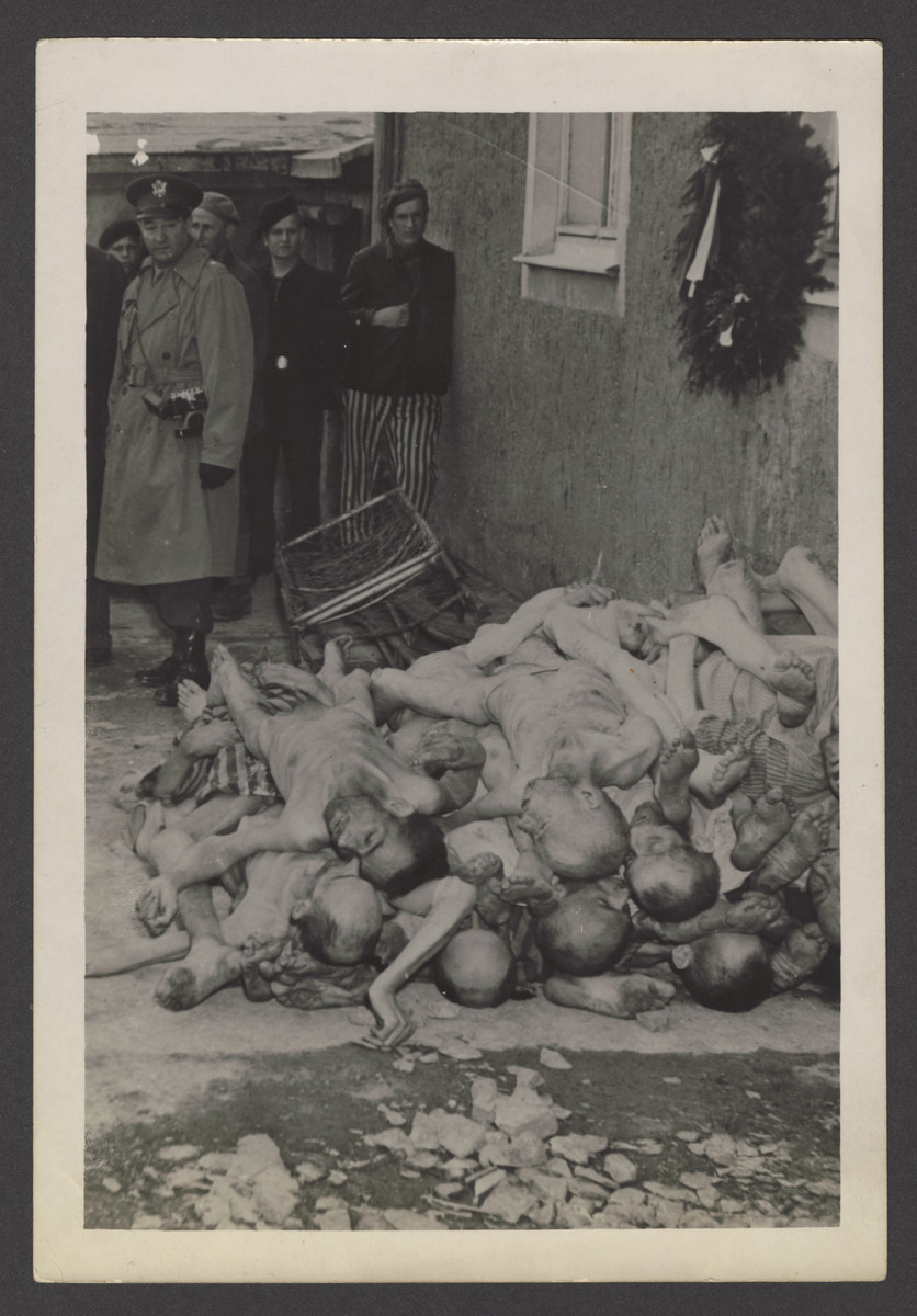 "American soldiers and survivors view corpses stacked near the crematoria at Buchenwald.  The inscription on the back of the photograph reads, ""Buchenwald."""