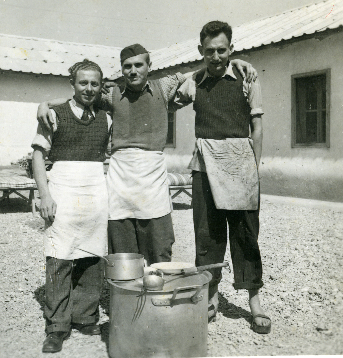 Three men pose behind a soup pot at Ferramonti.  Ernest Hellinger is probably the man in the middle.