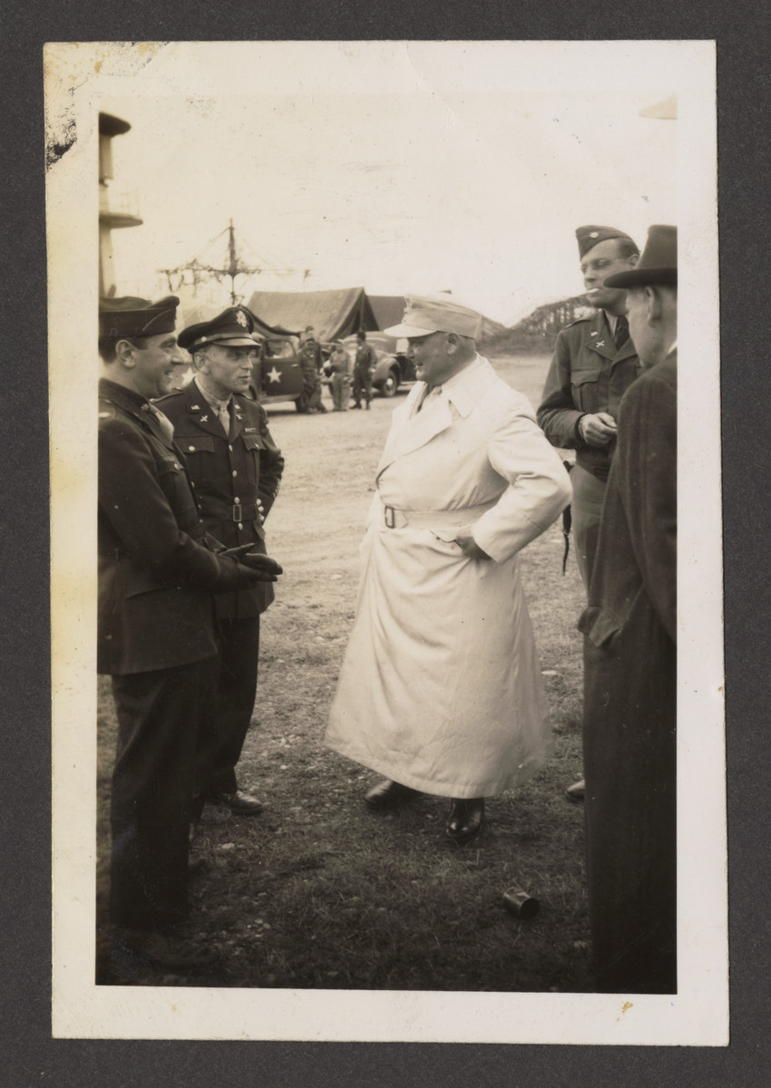 """Hermann Goering converses with American servicemen prior to boarding the plane to  Camp Ashcan, a temporary prisoner-of-war camp housed in the Palace Hotel at Mondorf-les-Bains, Luxembourg.   The inscription on the back reads, """"Herman in white greatcoat is an impressive looking slob."""""""