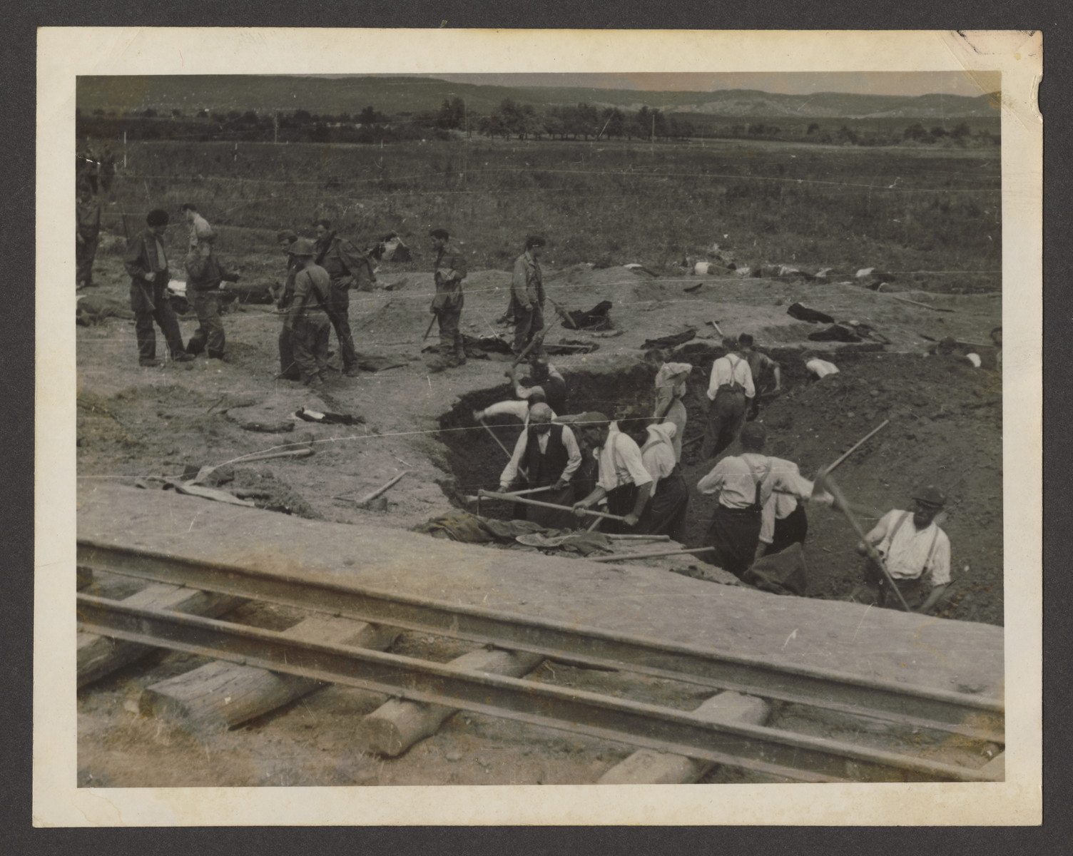 """American soldiers supervise German civilians forced to dig mass graves for the victims at Dachau.  The inscription on the back of the photograph reads, """" Dachau Camp, Germany."""""""