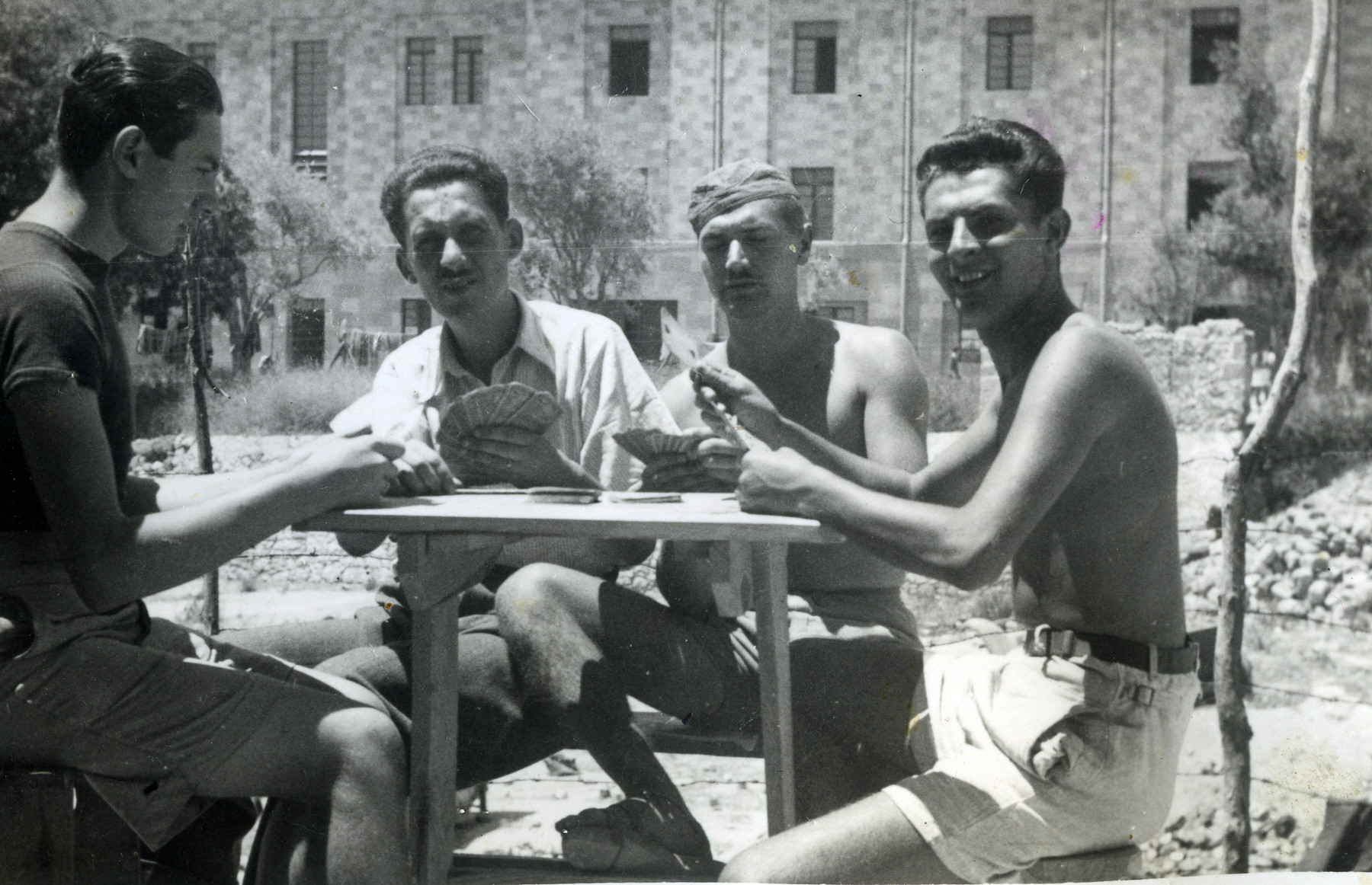 A group of men sitting outside playing cards at an unidentied location (possibly Rhodes).  Ernest Hellinger (probably second from the left) and Zoltan Yakubovich (probably far left) are pictured here.