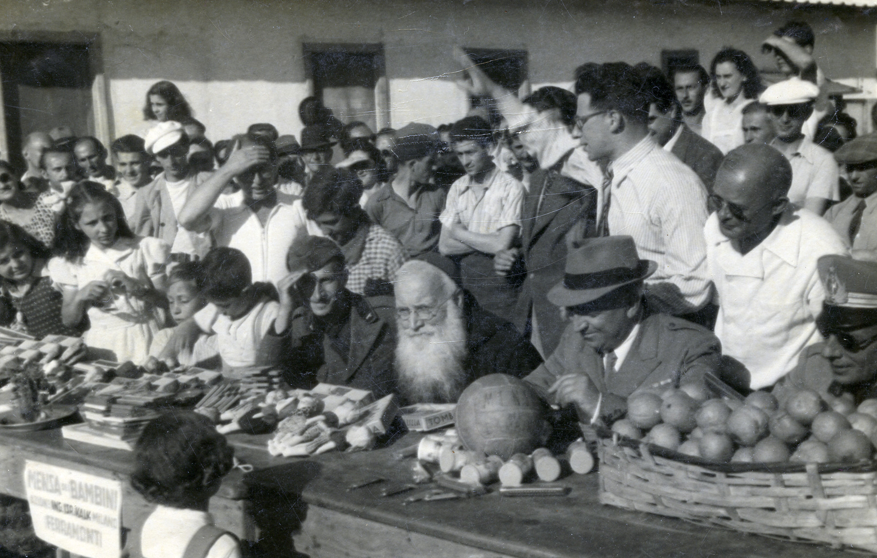 Internees at Ferramonti gather by a table displaying various goods.