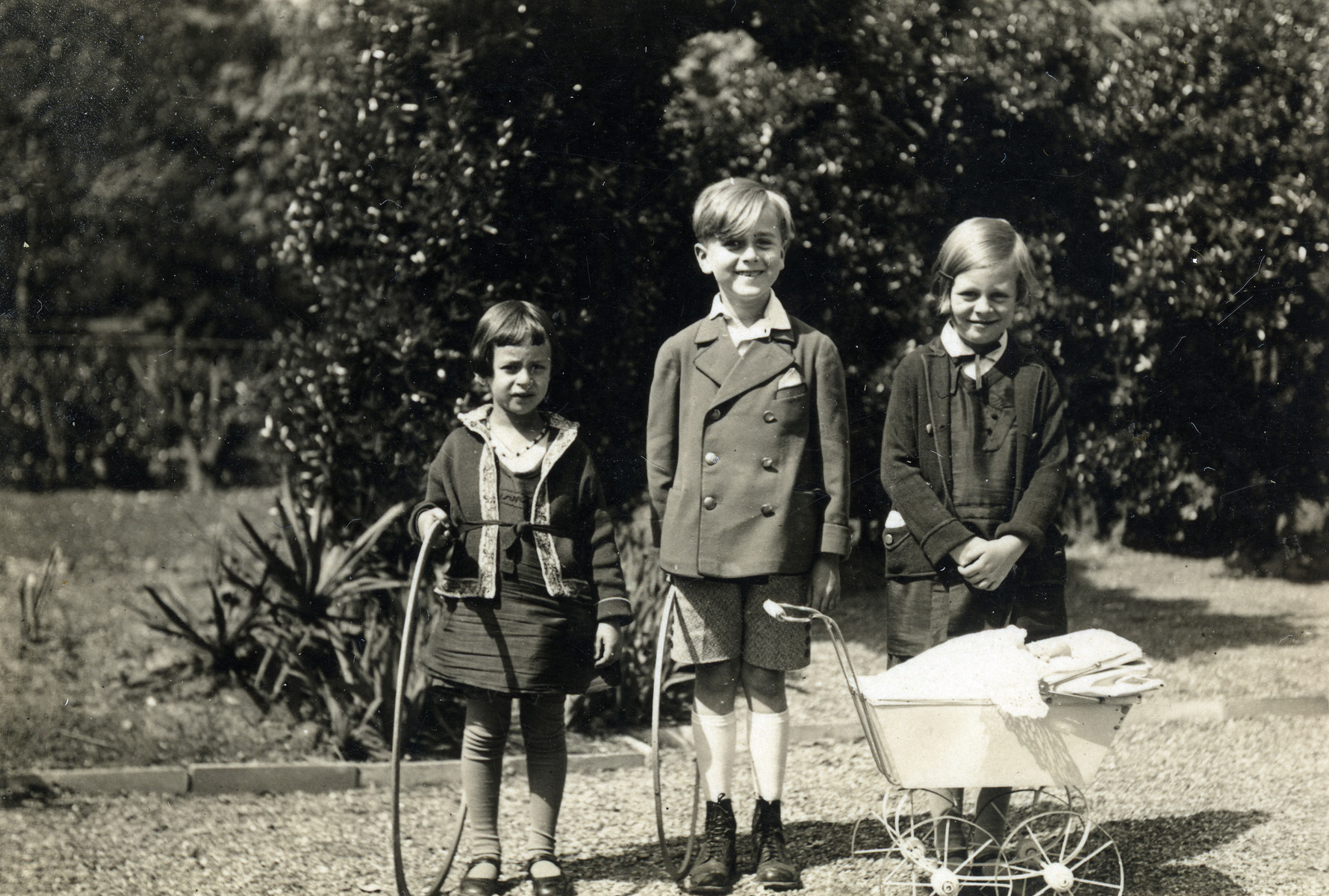 Anna Kohn (left) poses with two other children with hoops and a toy baby carriage.