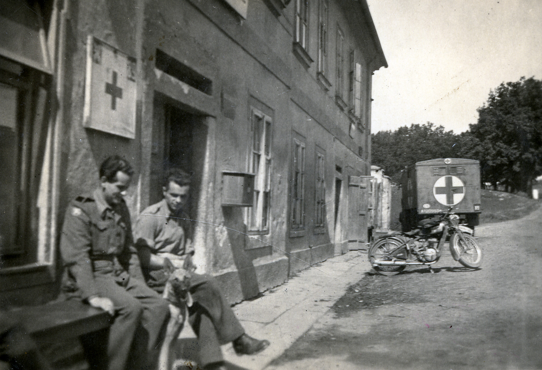 Two men sit outside a Red Cross building (possibly in France).  On the left is Zoltan Yakubovich wearing his Jewish Brigade uniform.