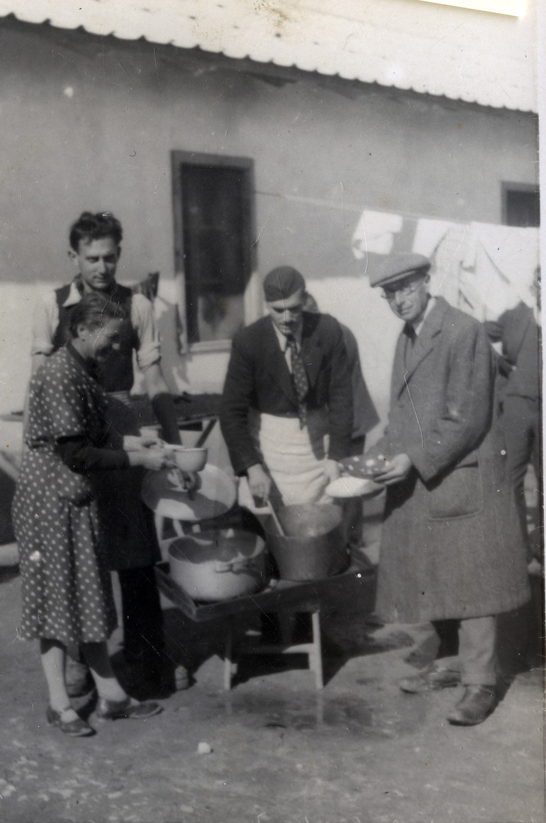 Ernest Hellinger serves soup to other internees in the Ferramonti internment camp.