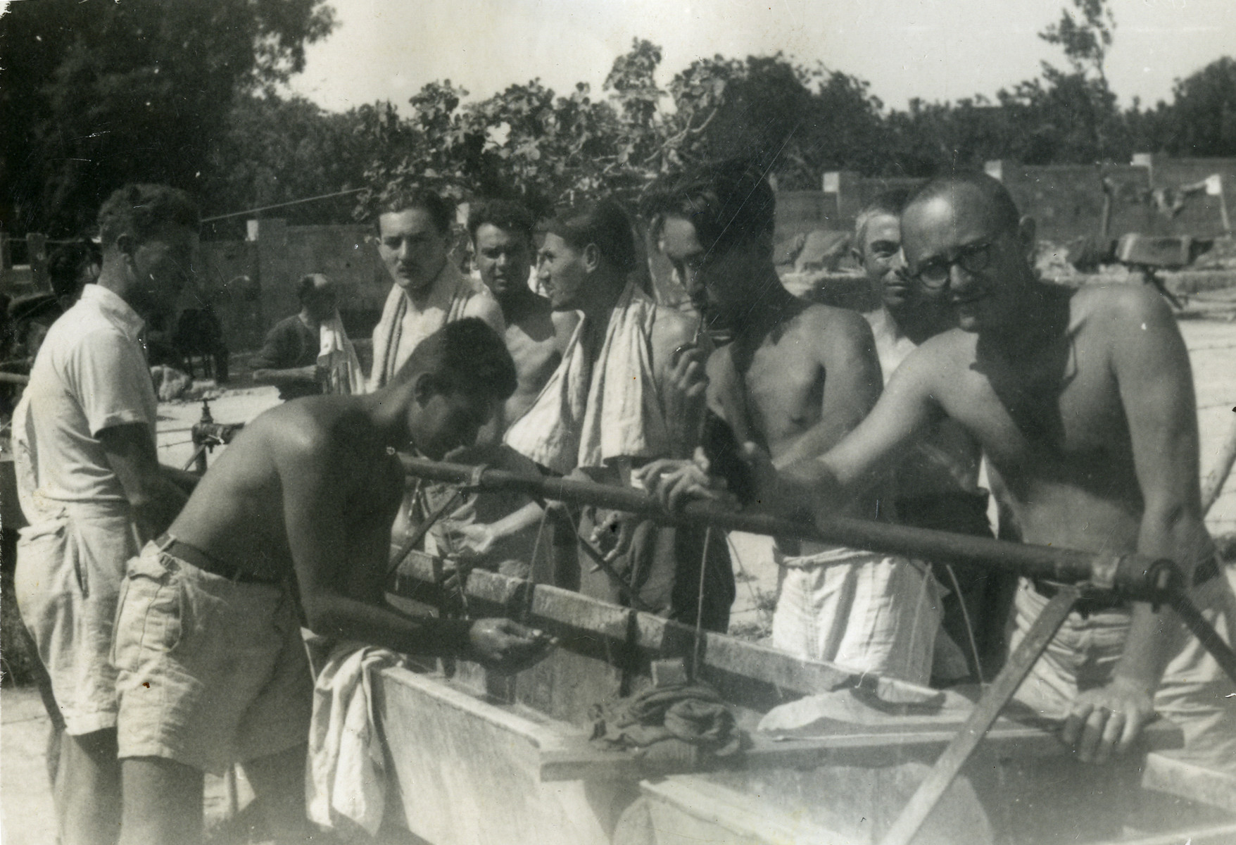 Survivors of the Pentcho wash up using the outside sinks, probably in Rhodes.