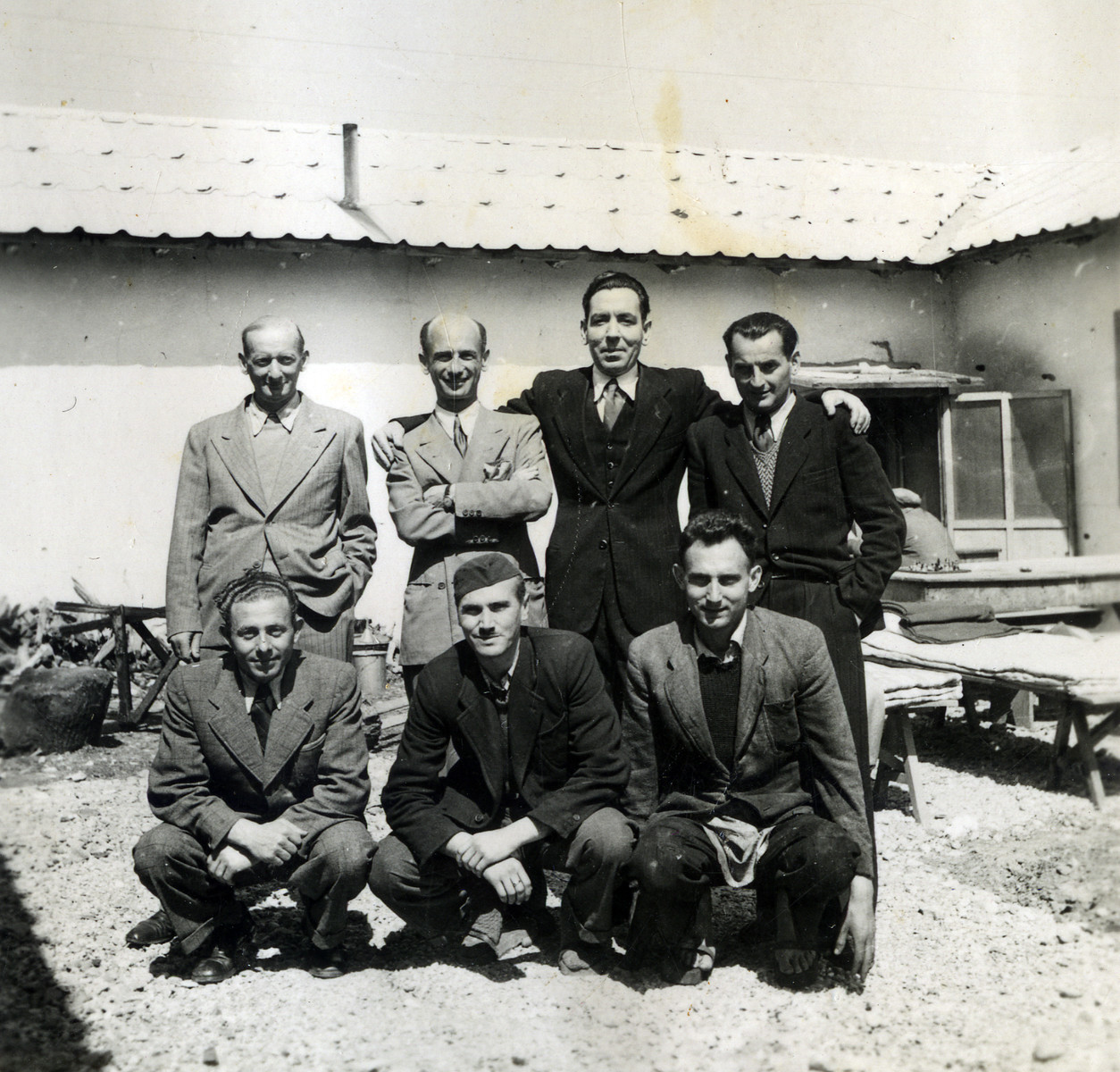 A group of men pose outside a building in Ferramonti.  Ernest Hellinger is probably in the front row in the middle.