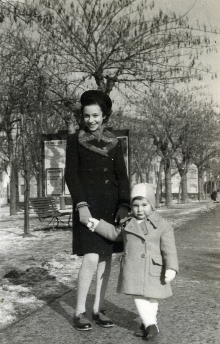 Anna Kohn poses on a tree lined path an with unidentified toddler.