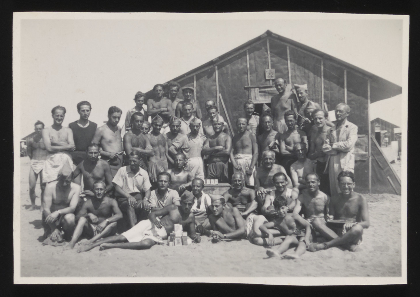Group portrait of prisoners in St. Cyprien  internment camp posing in front of a barracks.  Those pictured include Ludwig Cohn (donor's brother) and Fritz Tockus (donor's brother-in-law).