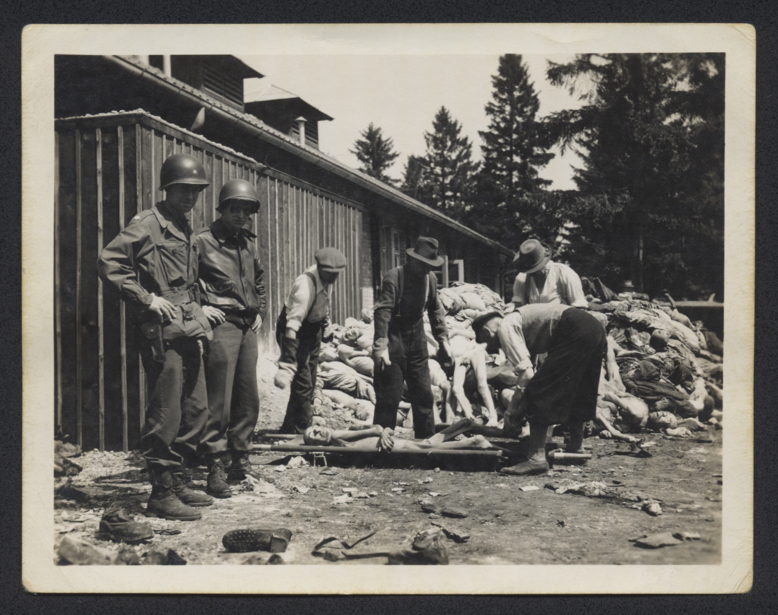 An American colonel and other soldier watch German civilians remove corpses piled behind the crematorium of the Dachau concentration camp.