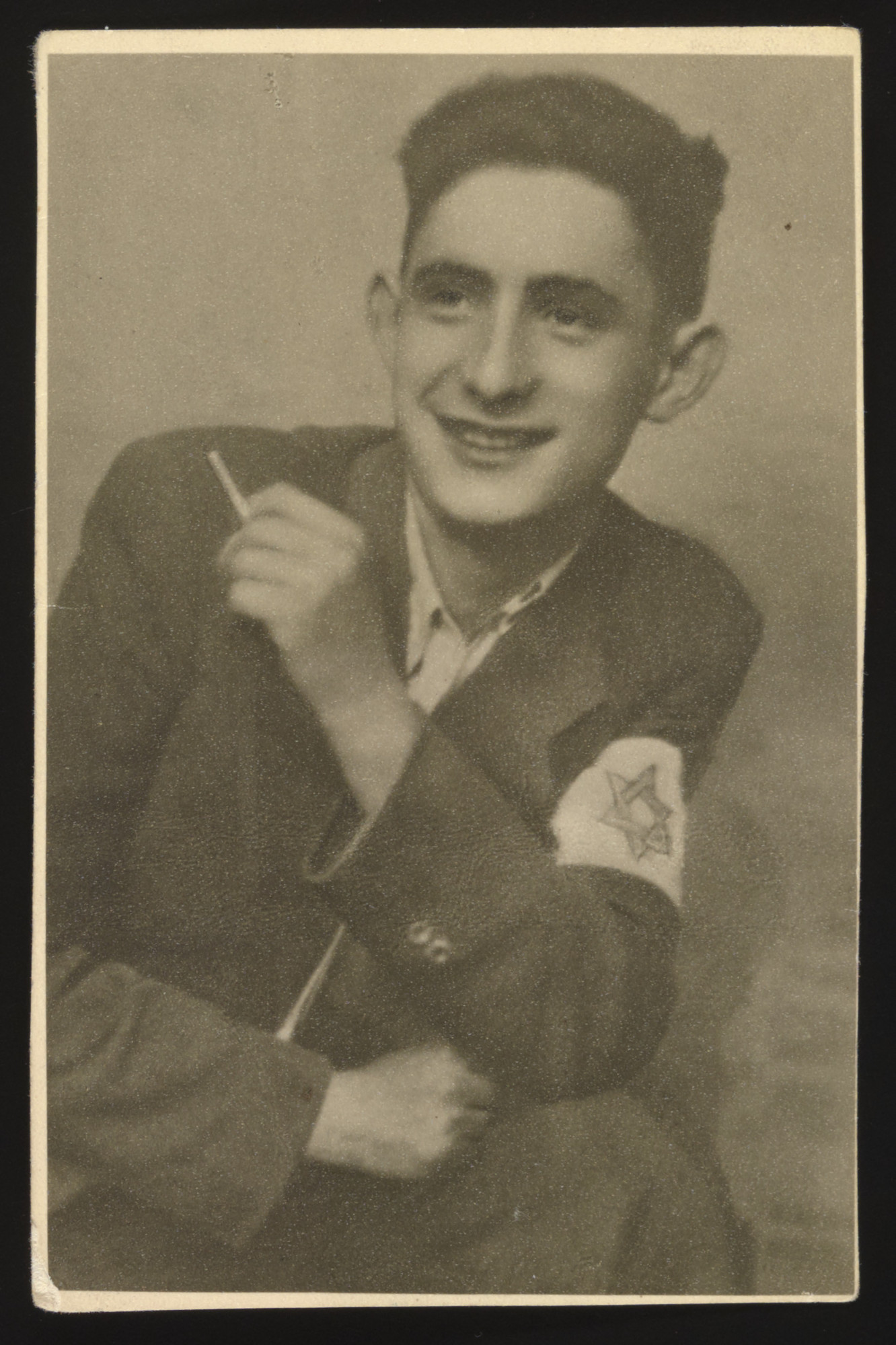 Close-up portrait of a young man wearing an armband with a Star of David holding a cigarette in the Radom ghetto.  Pictured is Szajek Birenbaum.  He worked in the ghetto as an electrician and perished in the Holocaust.