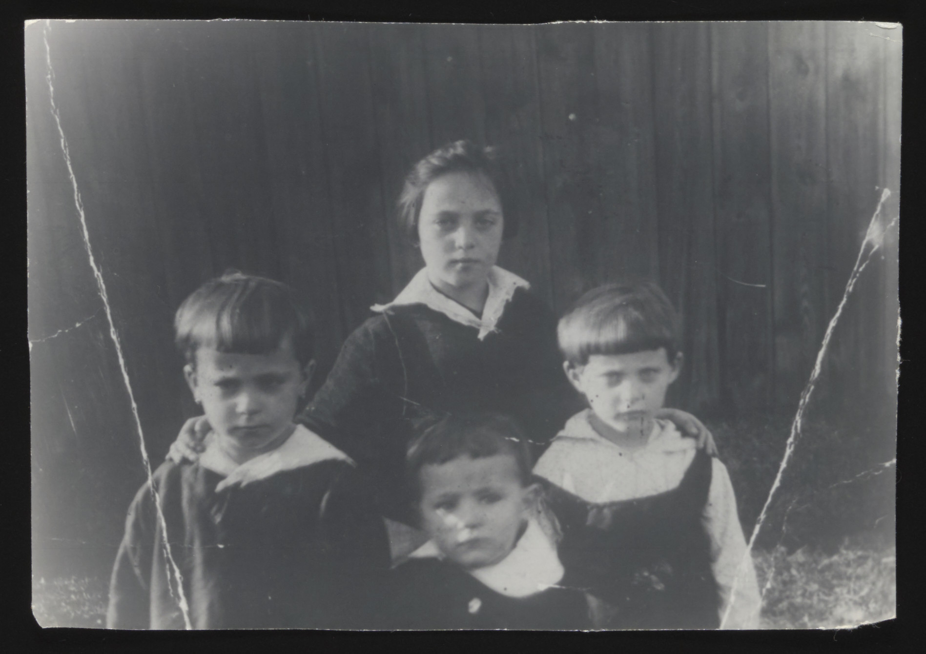 Close-up portrait of four Jewish children in prewar Radom.  Pictured are Lifcia Najman (standing).  In front are Gitel (left), Moszek and Edith.  Moszek perished in Auschwitz  at the age of 16.