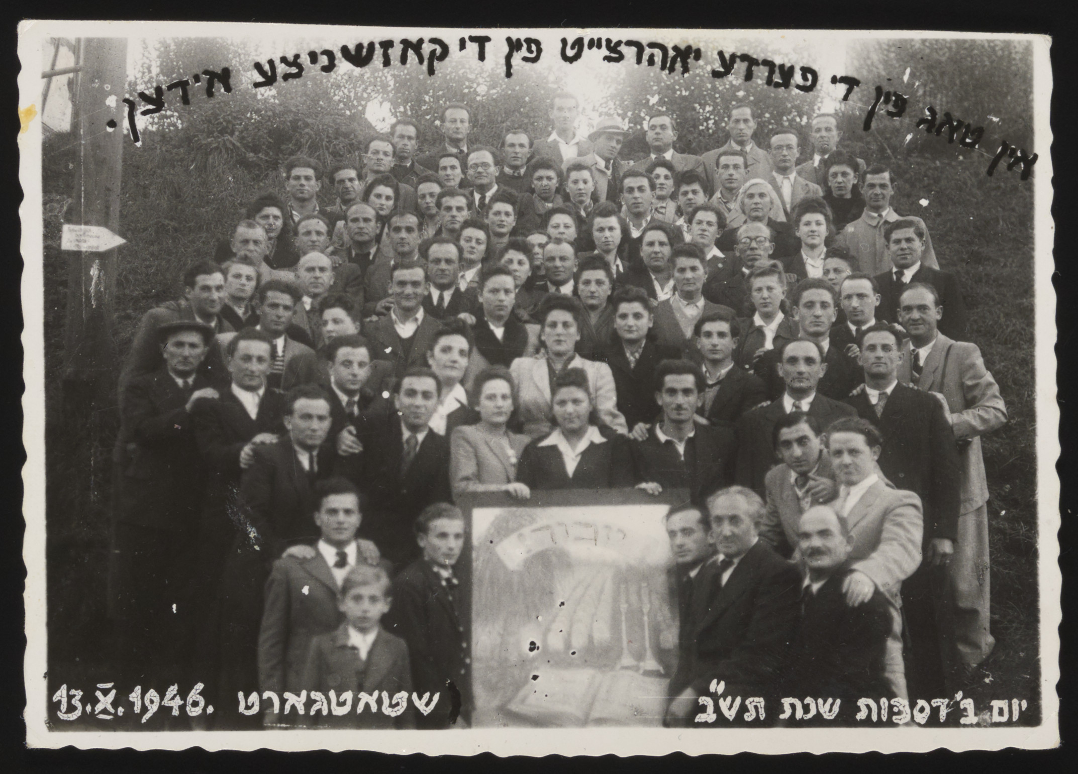 Survivors gather at the Stuttgart displaced persons camp to commemorate the fourth anniversary of the destruction of the Jewish community of Kozienice, Poland.  Laja Tenenbaum is pictured third row from the top, second from the right.  Also pictured is Zelda (Goldberg) Friedman, holding the Yizkor photo (woman on left).  Standing next to Zelda is Tsesha Eisenberg, a relative of Zelda's  from Kozienice.  Zelda was in Stuttgart, after the war and after marrying Yitskhak (Issak) Friedman, they made alliyah to British mandatory Palestine.