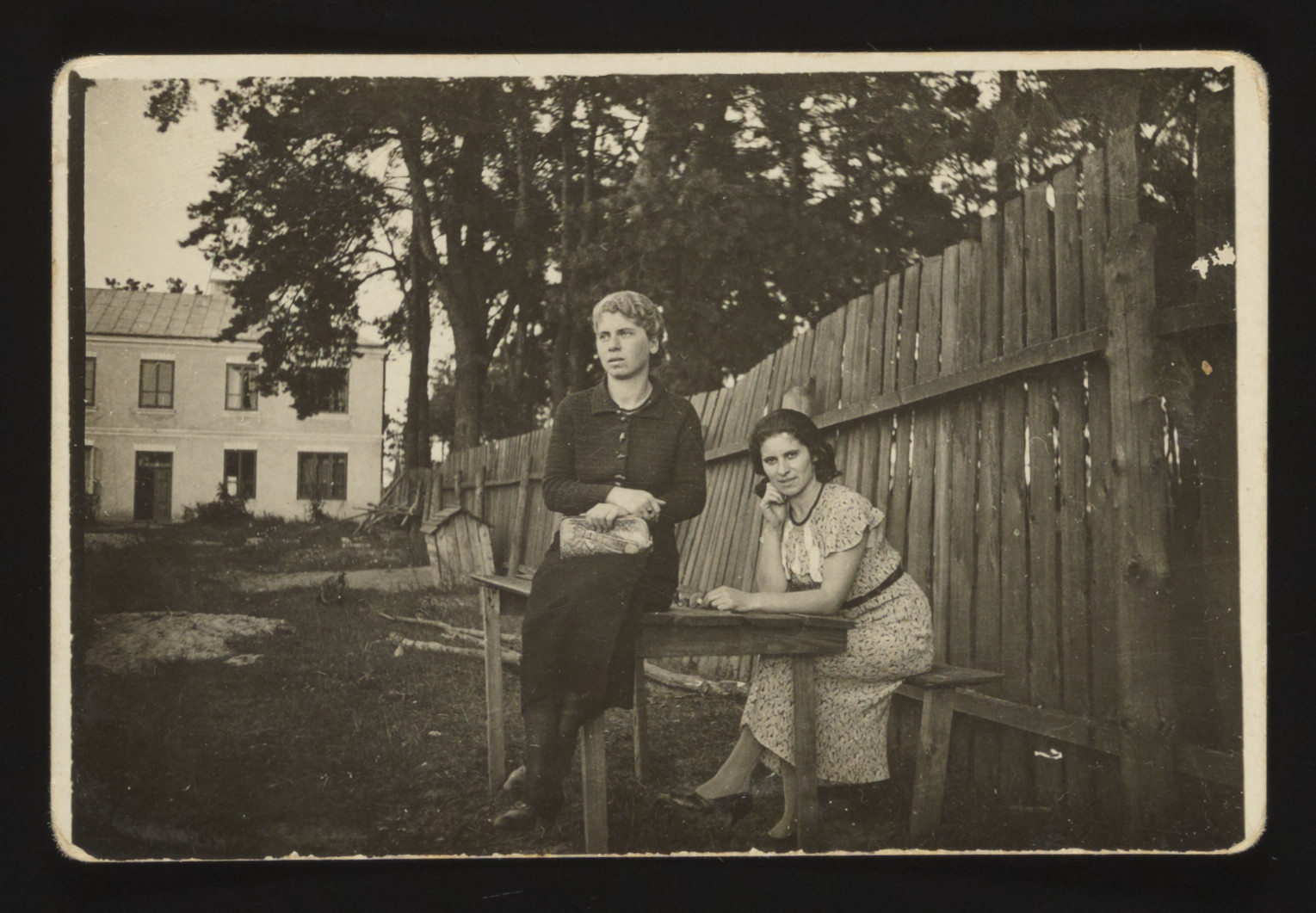 Two Jewish women from Kozienice sit on and next to an outdoor table by a wooden fence.  Pictured iare Gitl Szabason Weintraub who perished in Treblinka and Szprinca Szabason who left Poland for Palestine before the war.