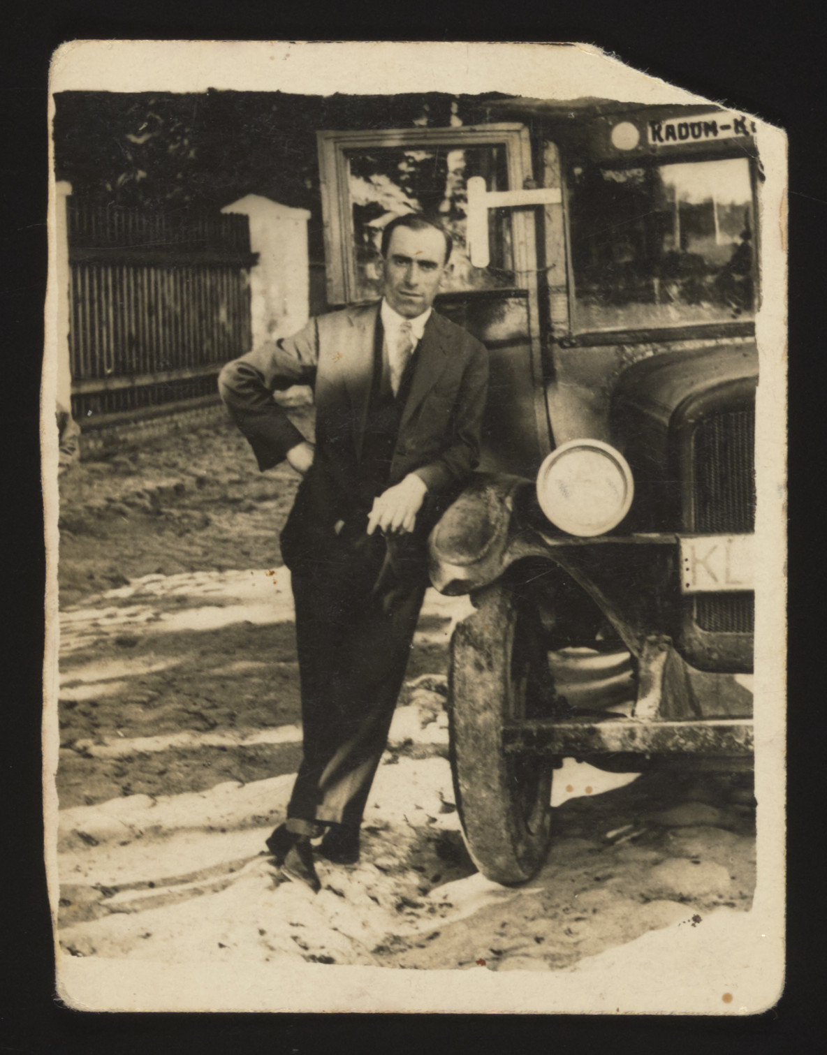 Mordechai, Rubinsztajn, the owner of the Radom-Kozienice Bus Line leans next to one of his buses in prewar Kozienice.    He later perished in Treblinka.