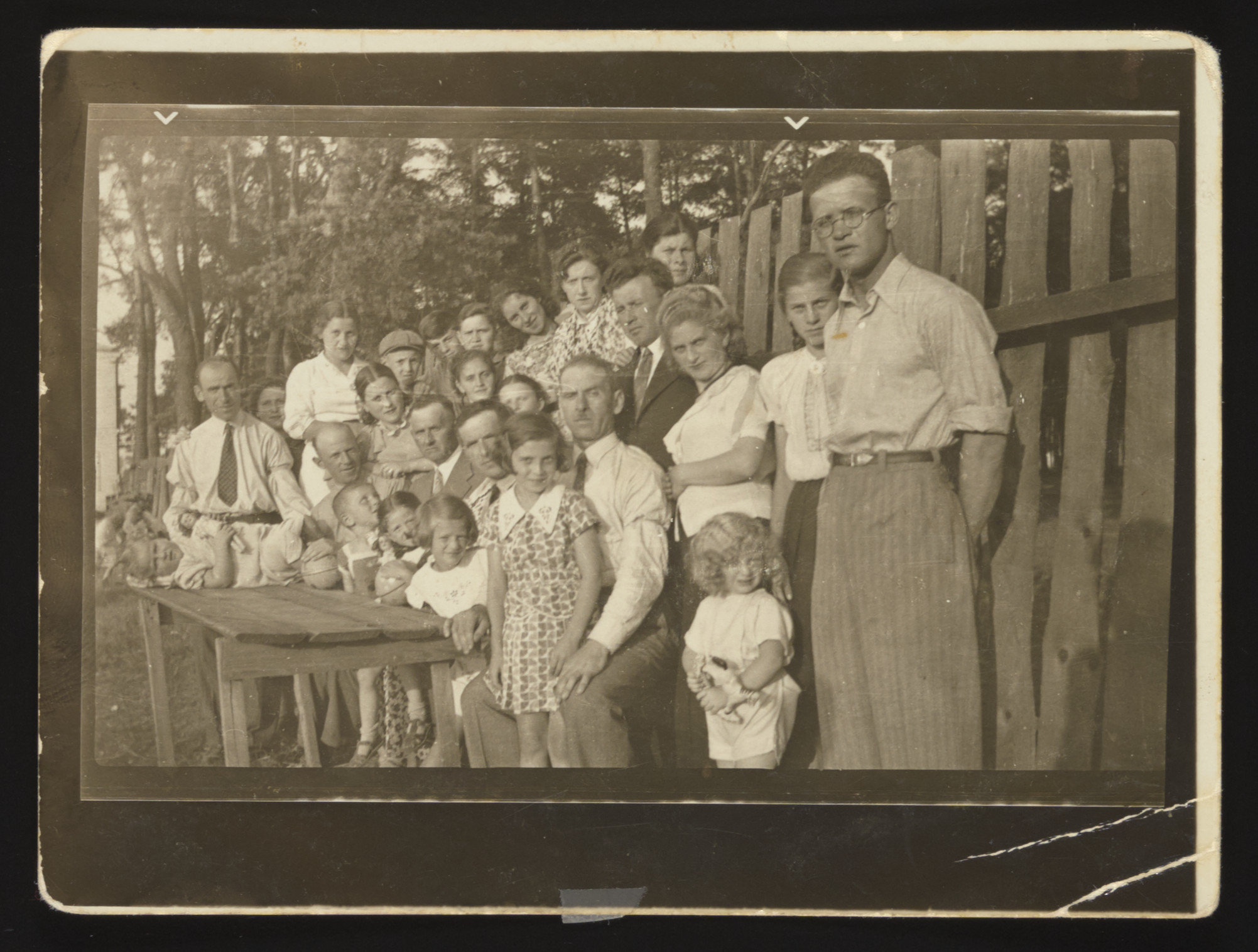 Group portrait of the Szabason family standing by a wooden fence in a yard in Kozienice on the occasion of a visit of Avrum Kestenberg from Colombia, South America.  Standing on the left is Mordechai Rubinsztajn (the donor's brother who perished in Treblinka).  The baby lying on the table is Geniusia Rubinsztajn who perished in Treblinka.  Standing second from the left is Chana Szabason Rubinsztajn who perished in Treblinka.  Seated second from the left is Zelig Szabason who perished and above him is Ruchl Szabason Rafalowicz who survived.  Avrum Szabason is seated first from right; Esther Szabason stands in front.  The little blond boy, Szaja Shau, survived in hiding and above him is Molly Szabason Shau who perished.  Lewek Szabason is standing on the far right, and his cousin Edzia Kestenberg who survived on false papers is next to him.