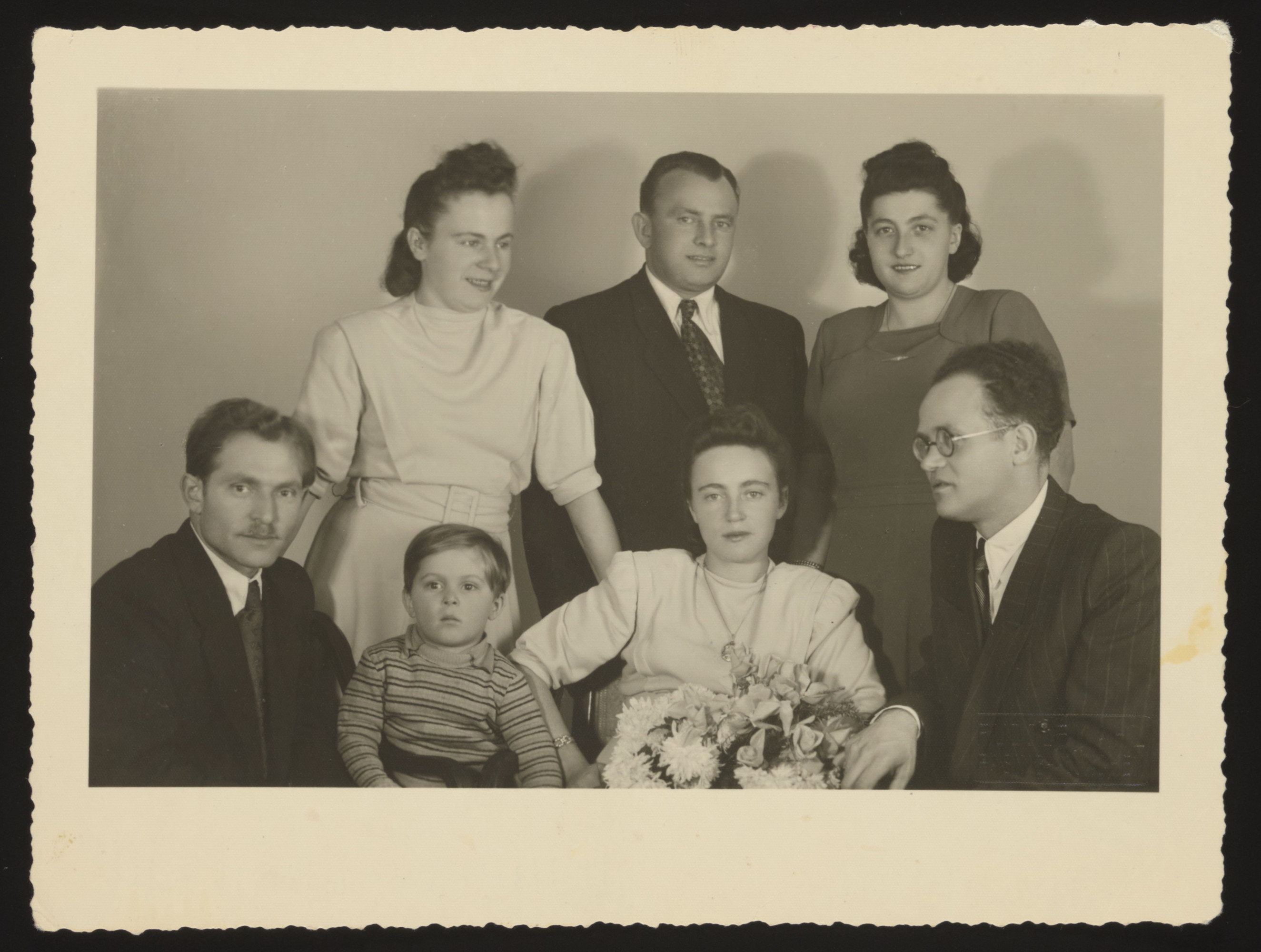 Group portrait of a Jewish family and friends celebrating a wedding in Munich after the war.  Pictured (standing from left) are Etel Najman Zilbersztok, Jakub and Hanka Mandelbaum.  Seated are Herszl Zilbersztok, Heskel Zilbersztok, Lifcia Najman (the bride) and Lewek Szabason (the groom).