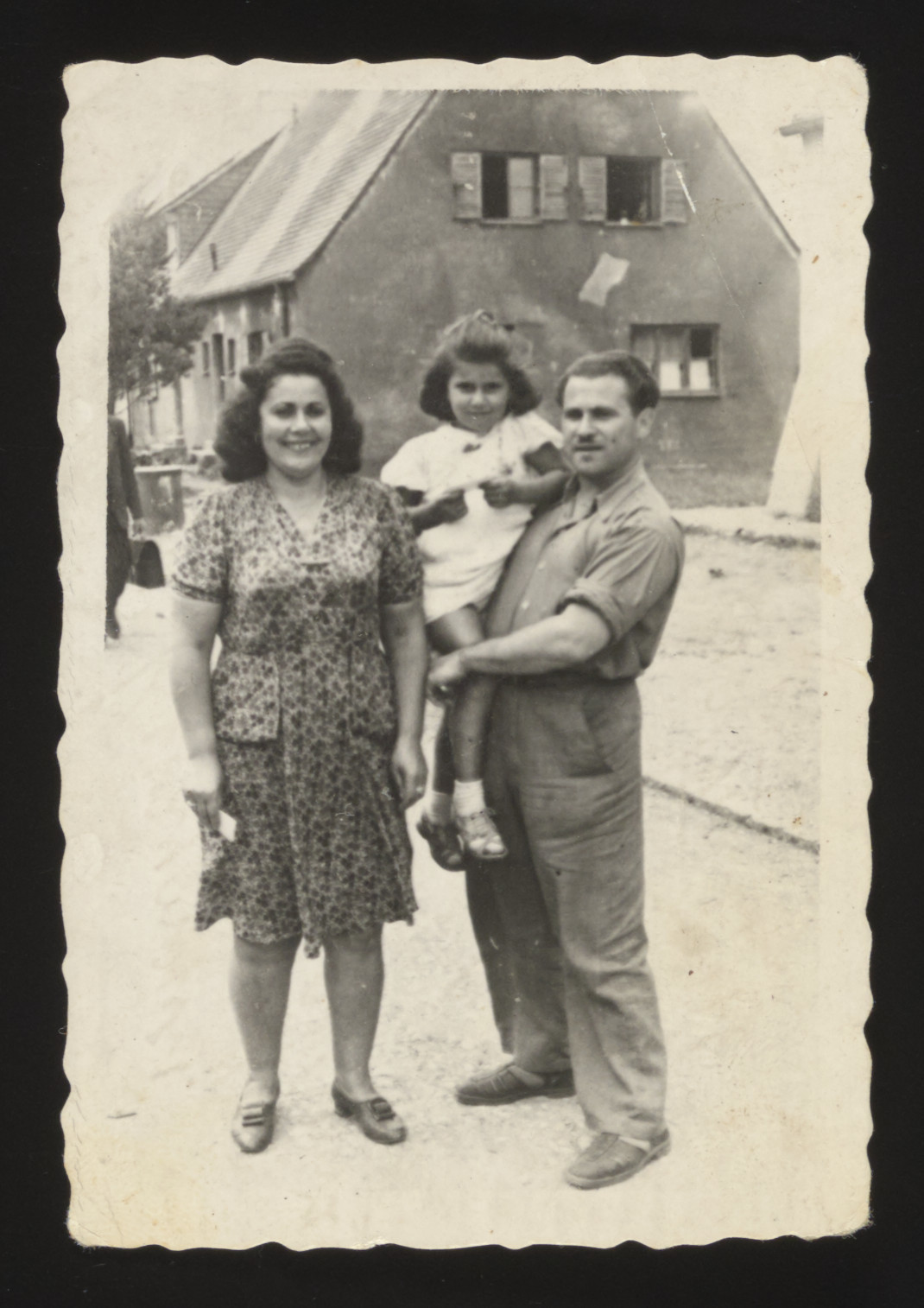 """Portrait of a Jewish couple and their daughter standing in front of a home in Thorn (Torun).  Pictured are Genia and Chil Heniek Szabason.  The caption reads """"To my dear cousin on the day we left Thorn, from Heniek."""""""
