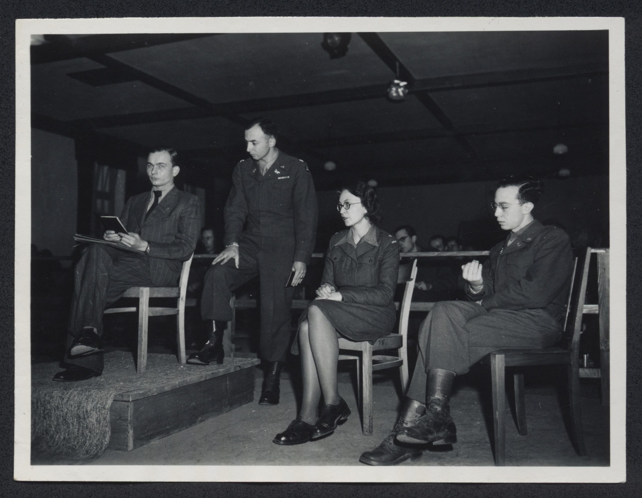 Prosecution witness Michael Pellis, a former inmate at Dachau, testifies at the Dachau trial.  Pictured second from the left is prosecuting attorney Lt. Colonel William Denson.