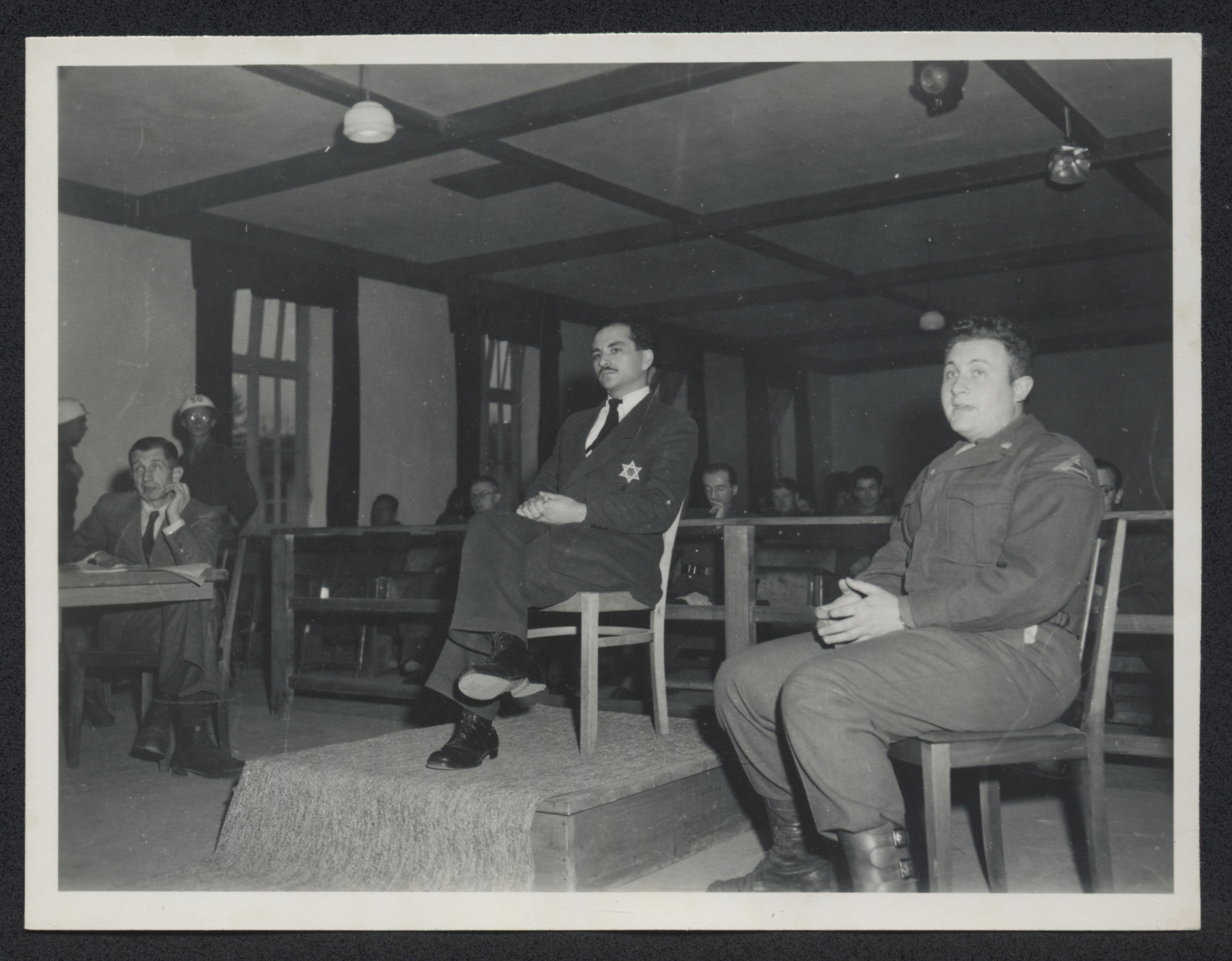 A witness wearing a star of David on his suit jacket testifies during the Dachau war crimes trial.