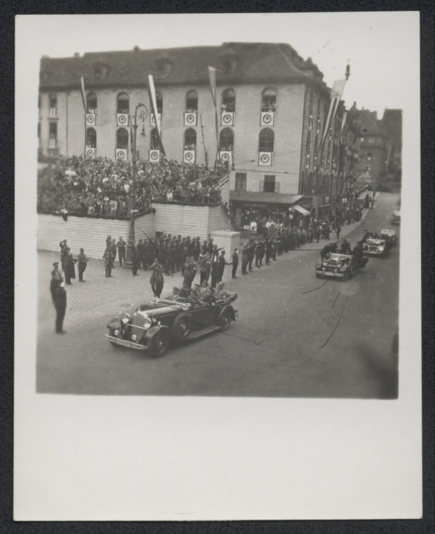 Nazi party officials drive past stands of spectators, probably during Reich Party Day in Nuremberg.