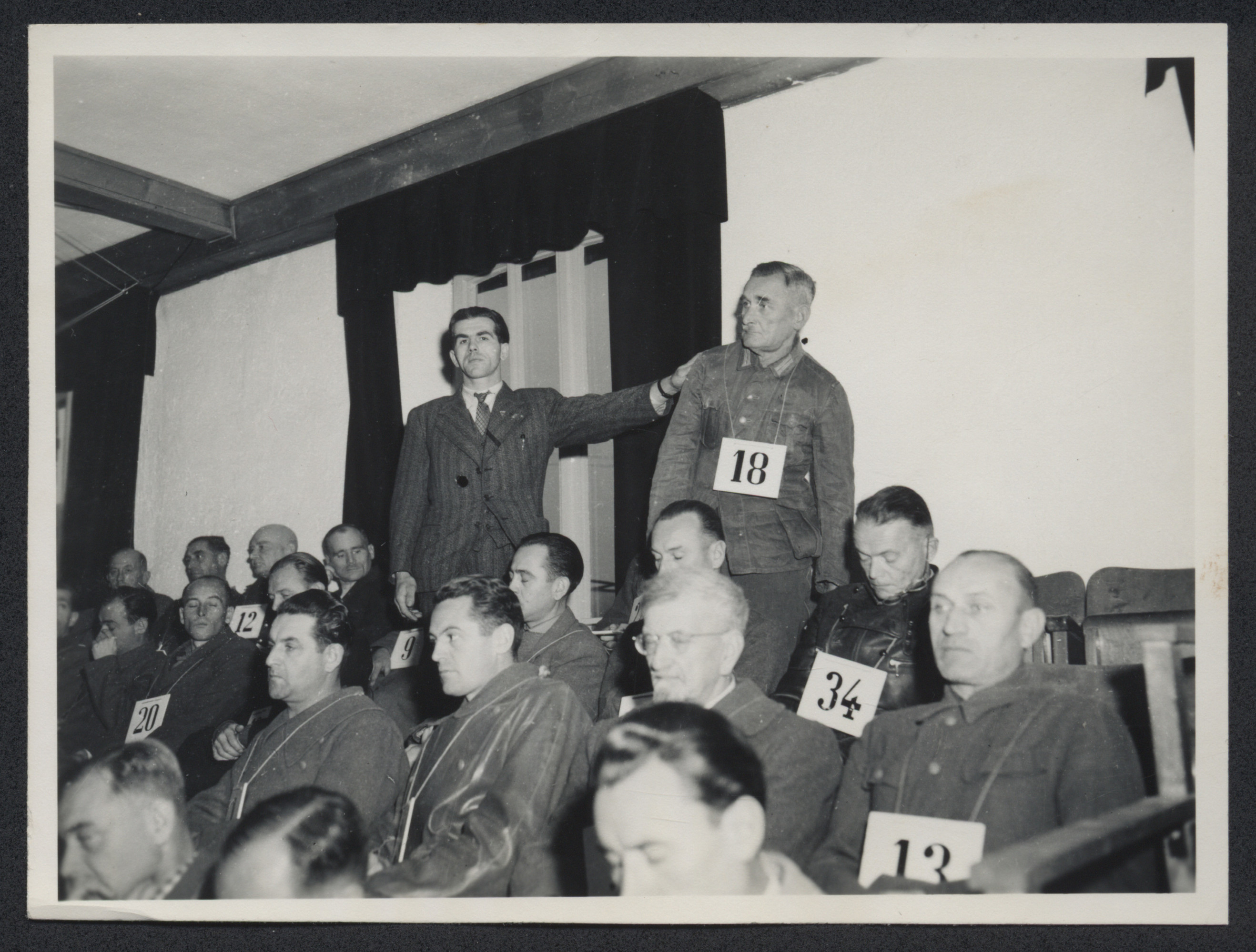 Prosecution witness Michael Pellis, a former inmate at Dachau, identifies SS Hauptscharfuerher Franz Boettger at the Dachau trial.    Also pictured are defendants Walter Adolf Langleist (#34), Otto Foerschner (#13), Anton Endres (#20), Johann Baptist Eichelsdorfer (#12), and Dr. Kalus Schilling (in front of Boettger).