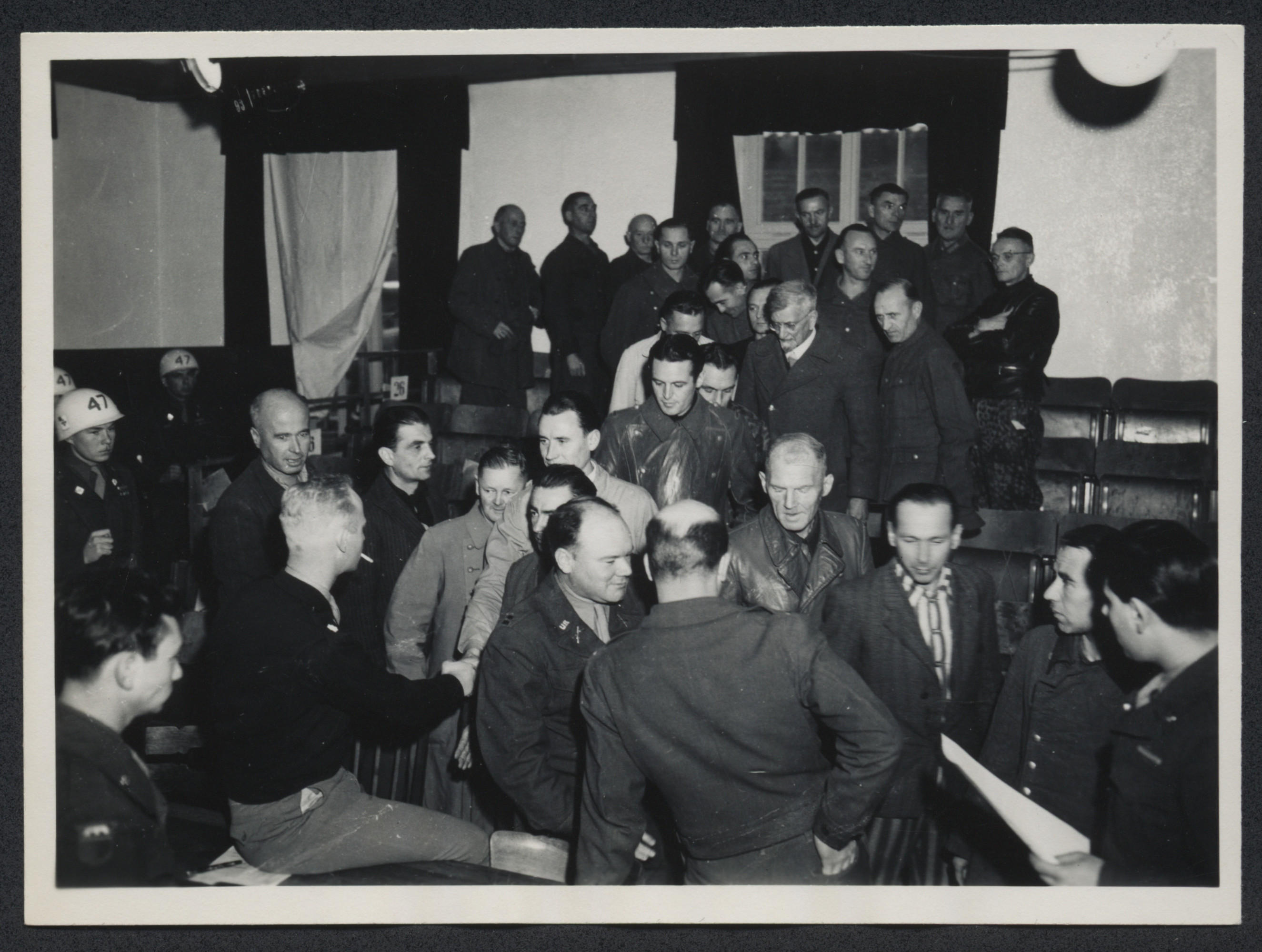 Proceedings of the Dachau concentration camp trial.  Among those pictured are defendants Dr. Klaus Schilling (center right of photograph, wearing glasses), and Emil Erwin Mahl (wearing prisoner uniform under suit jacket).