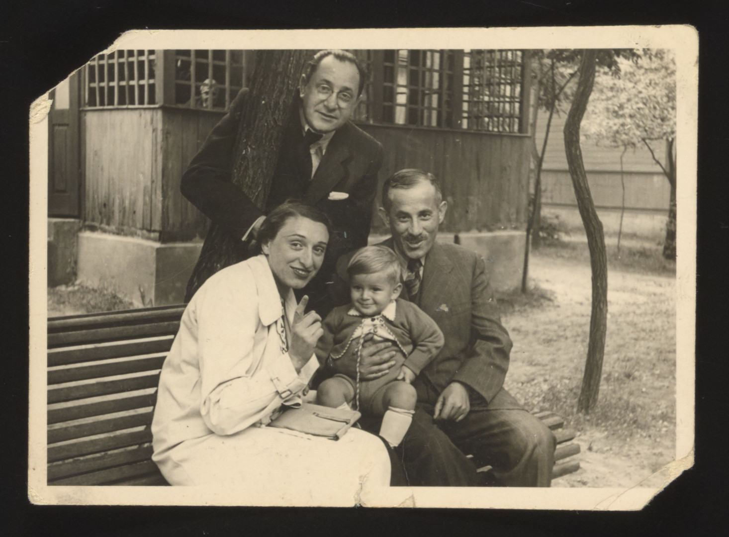 Portrait of a Polish Jewish family sitting on a bench in Wisniowa Gora shortly before the start of World War II.  Among those pictured are Marcel Rozenberg (standing back), his brother and sister-in-law and his young son Stefan.