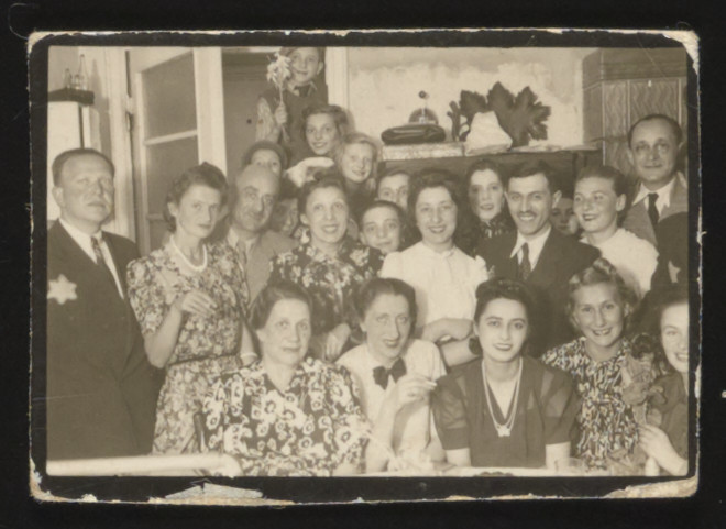 Group portrait of friends gathering in a home in the Lodz ghetto.  Among those pictured are Marcel Rozenberg (standing upper right ) and Bernard Fayner (first from left).