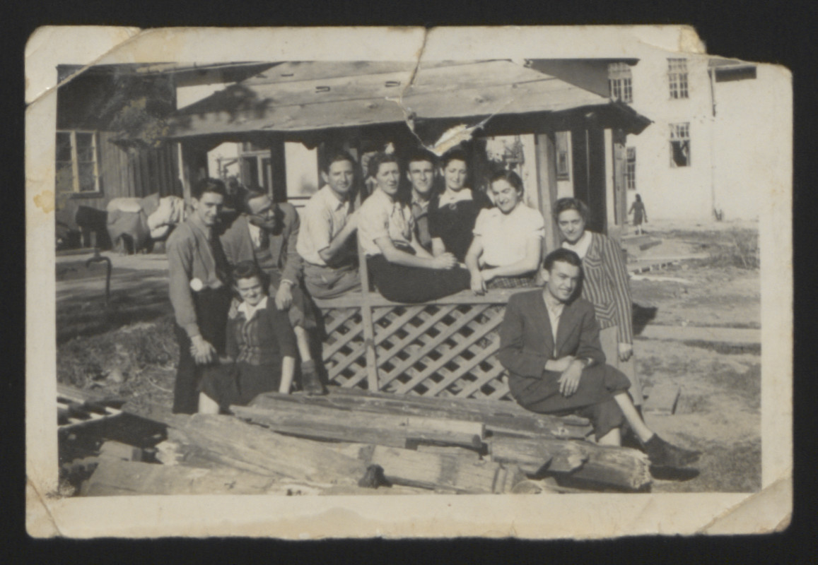Group portrait of young people posing around a wooden shelter in Boryslaw.   Among those pictured are the donor's aunts, Rozka Pomeranz (third from the right) and Julka Pomeranz (second from the right).