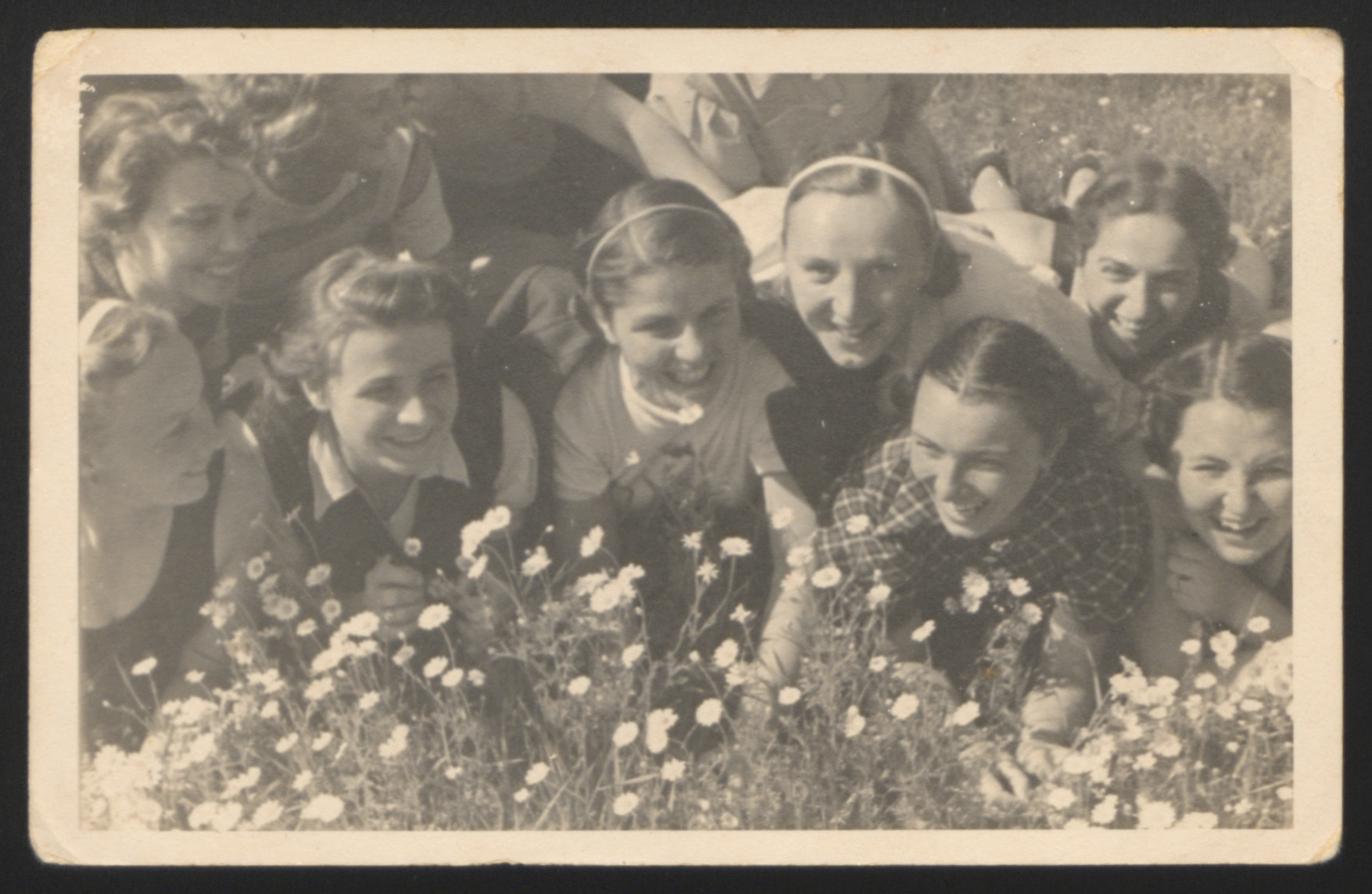 """Girls attending the School of Physical Education """"CIF"""" in Warsaw pose for a photograph while lying on a field.   Among those pictured is Rozka Pomeranz, donor's aunt (right corner)."""
